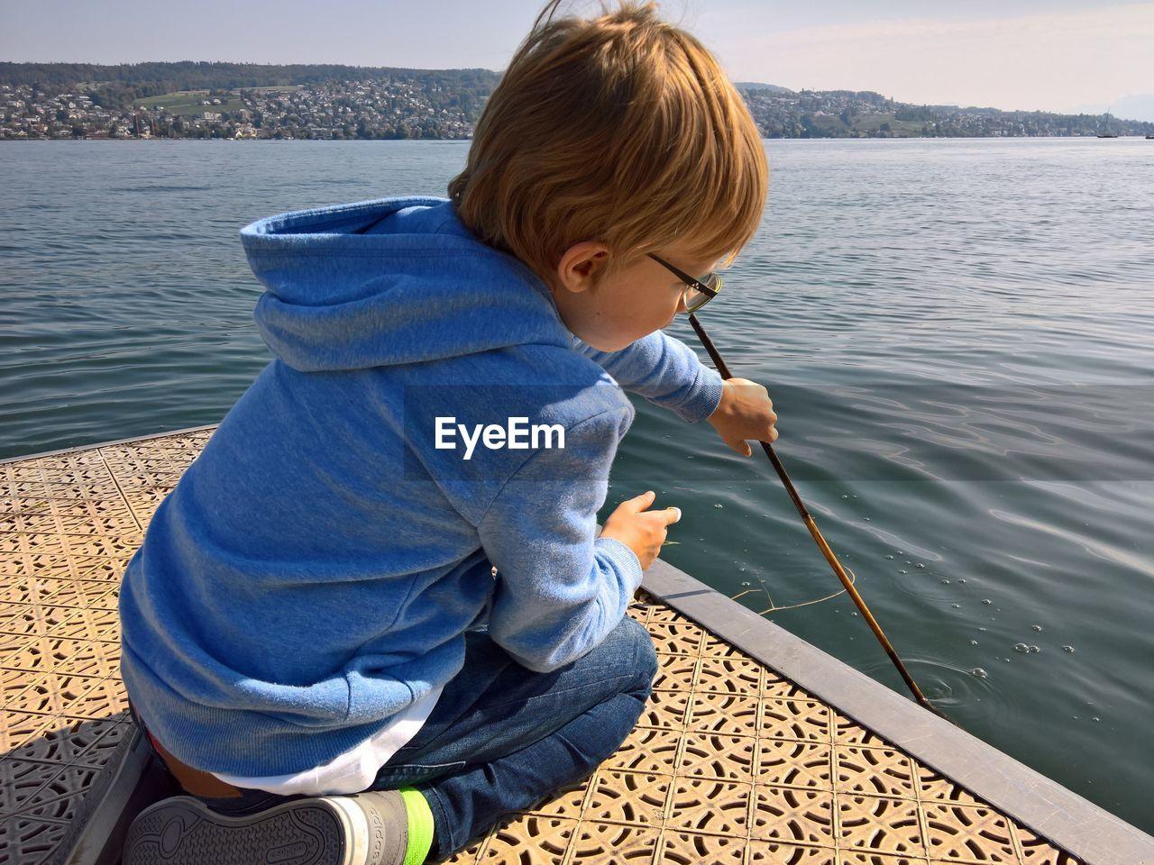 Boy Holding Stick By Lake