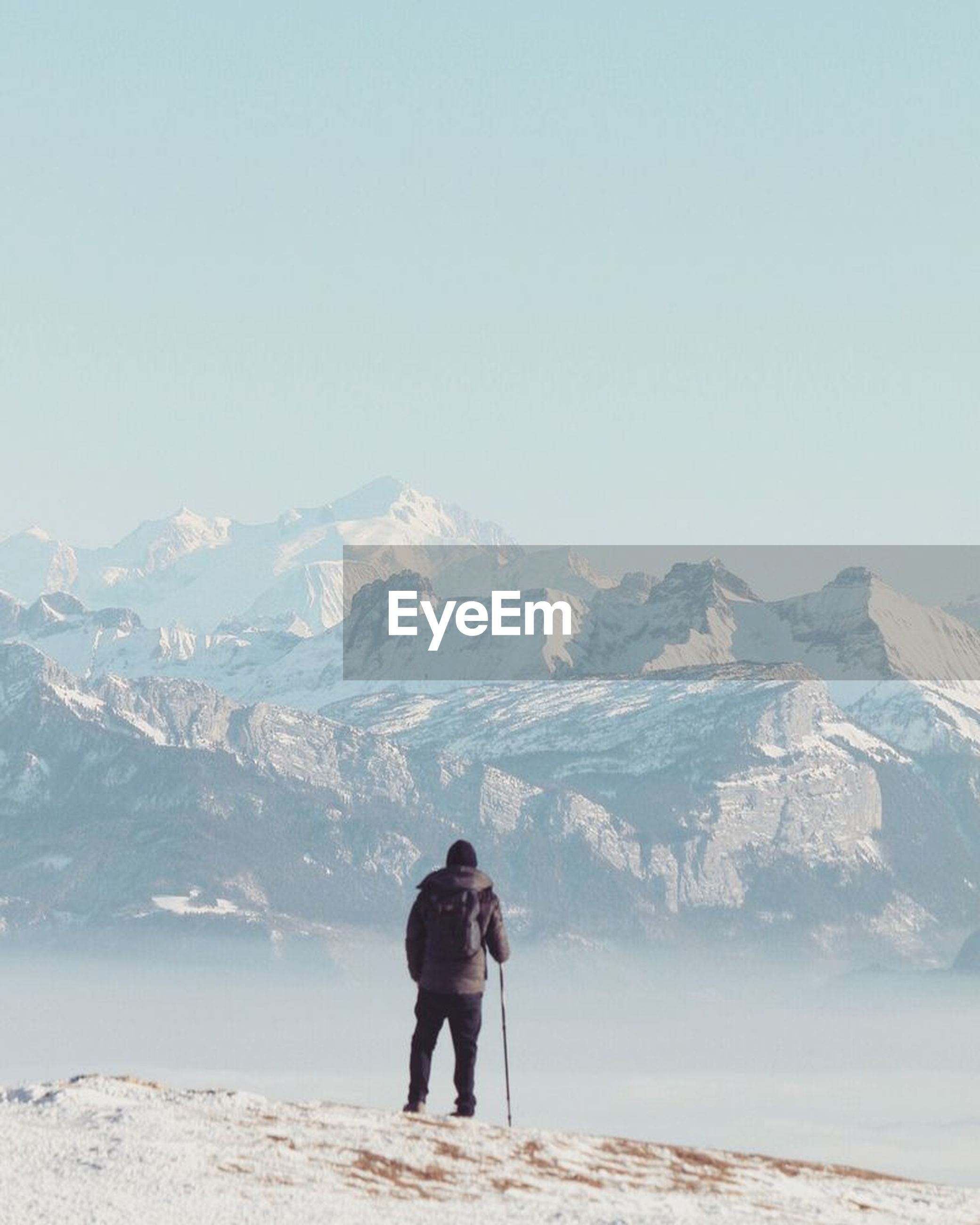 rear view, mountain, real people, full length, leisure activity, nature, copy space, one person, adventure, winter, beauty in nature, mountain range, lifestyles, standing, snow, hiking, scenics, vacations, cold temperature, day, outdoors, clear sky, warm clothing, women, men, sky, adult, adults only, people