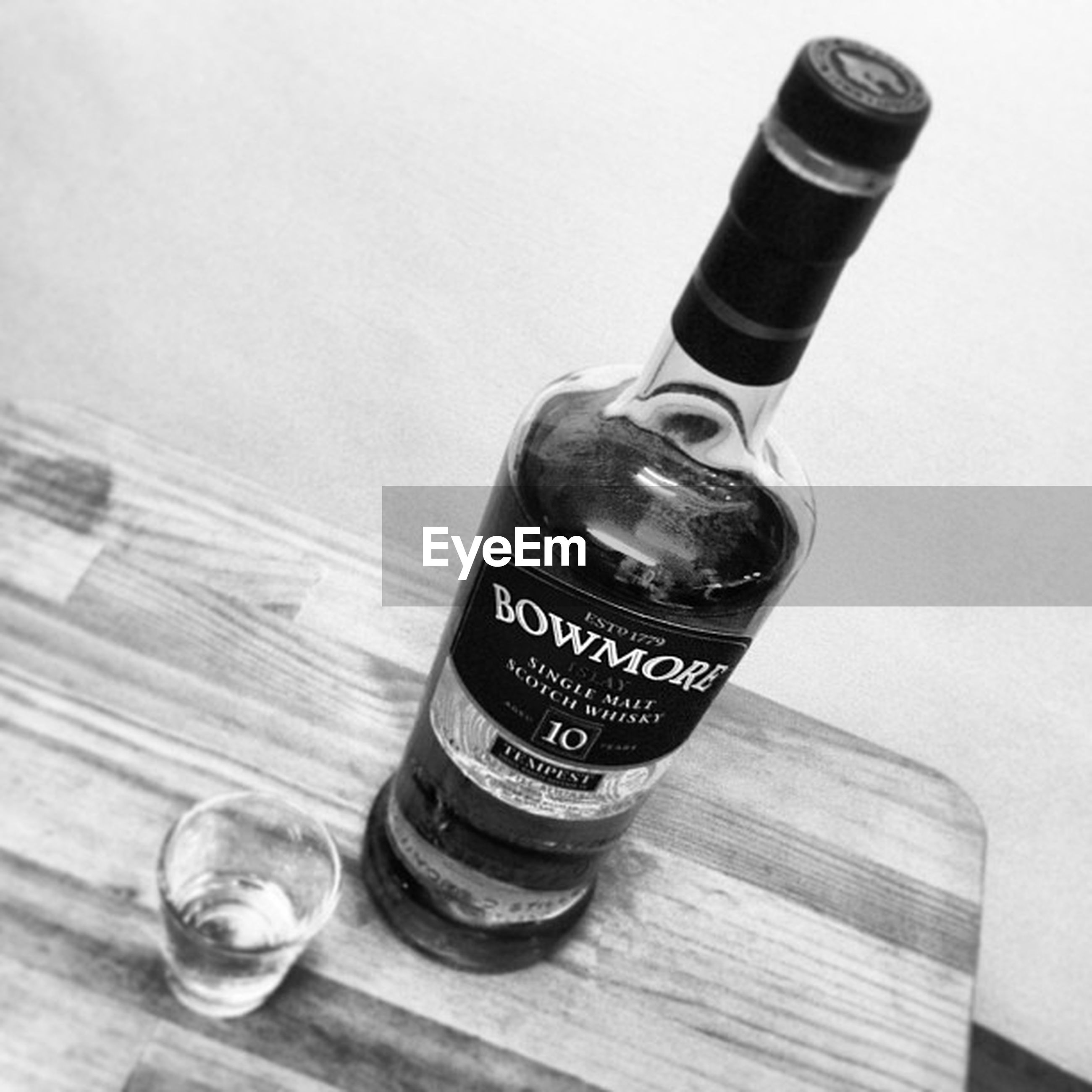 indoors, still life, table, close-up, text, communication, bottle, western script, wood - material, studio shot, high angle view, single object, food and drink, drink, white background, refreshment, no people, metal, alcohol, selective focus