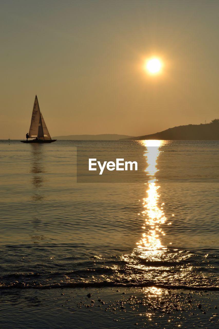 water, sky, sea, sunset, sun, scenics - nature, beauty in nature, reflection, orange color, tranquility, tranquil scene, nature, sunlight, idyllic, horizon, land, horizon over water, nautical vessel, beach, sailboat, outdoors, no people