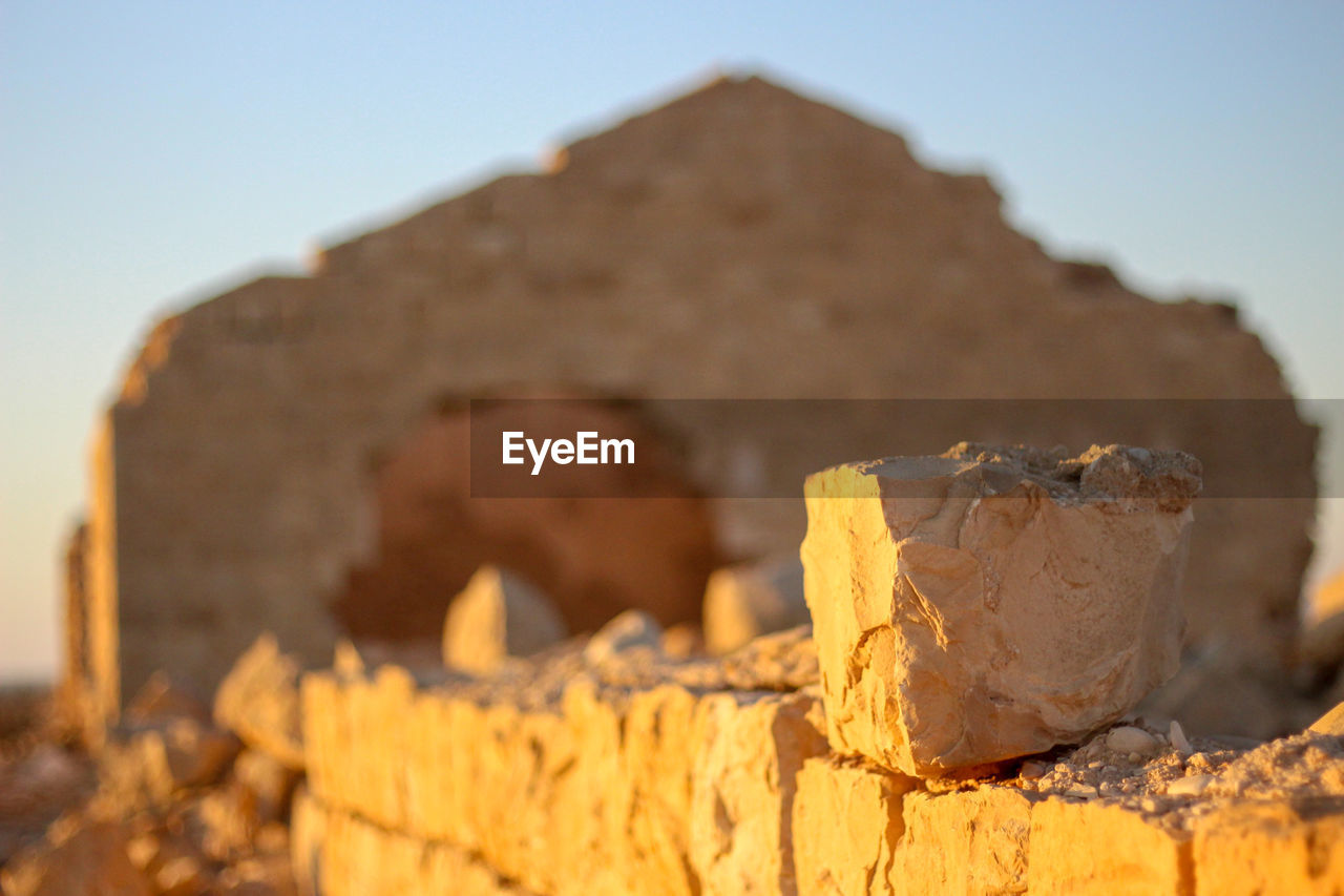 focus on foreground, close-up, no people, nature, day, outdoors, solid, still life, architecture, built structure, food and drink, rock, rock - object, yellow, sunlight, broken, wood - material, food, textured, brown