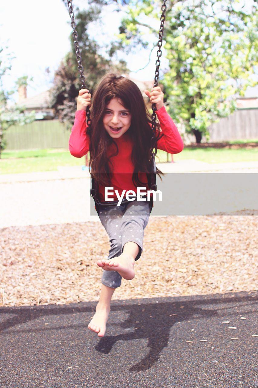 Portrait of playful girl swinging at park