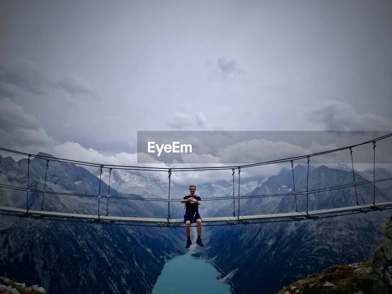 Man sitting on footbridge over mountains against sky