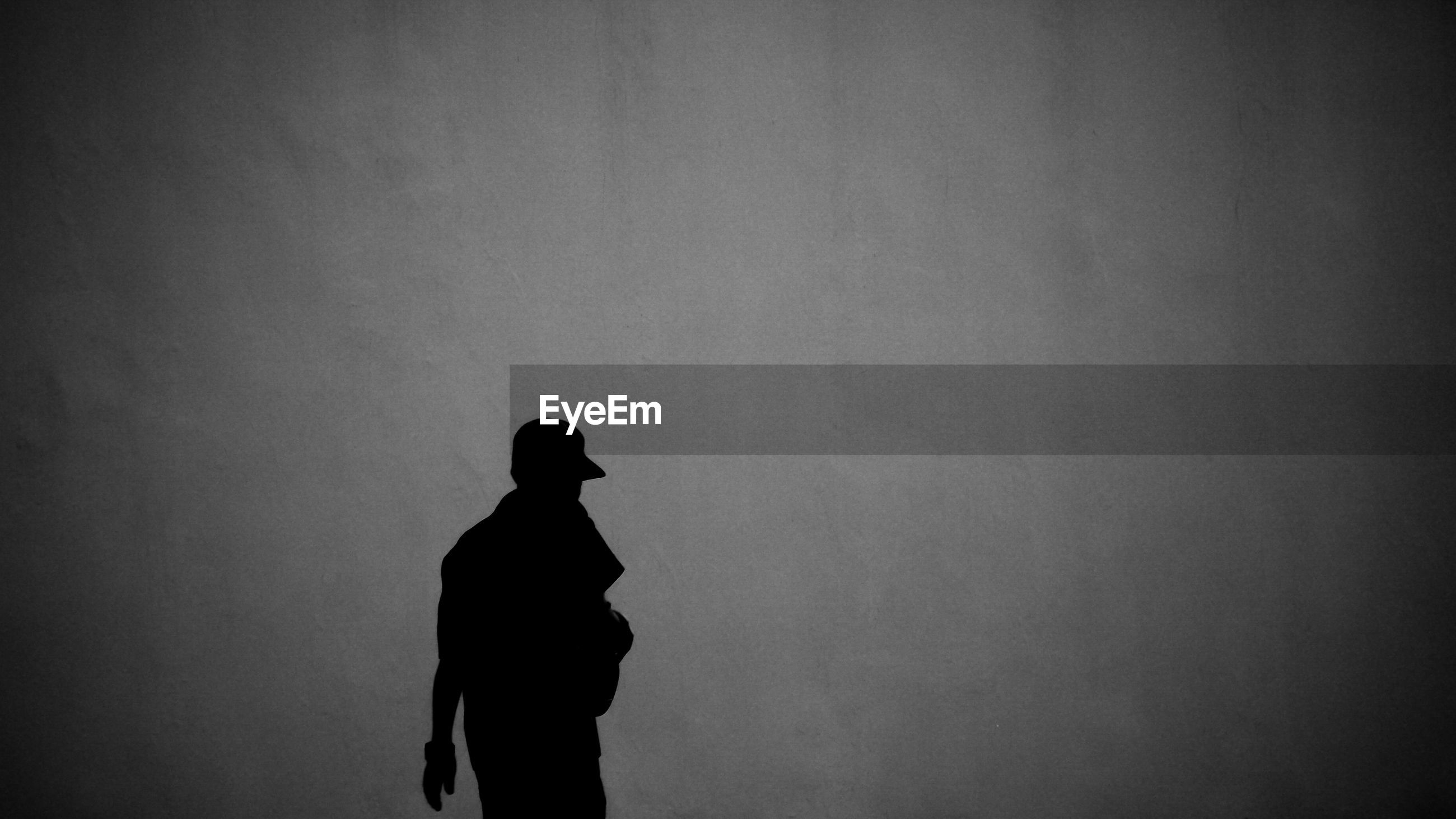 SILHOUETTE MAN STANDING BY WALL