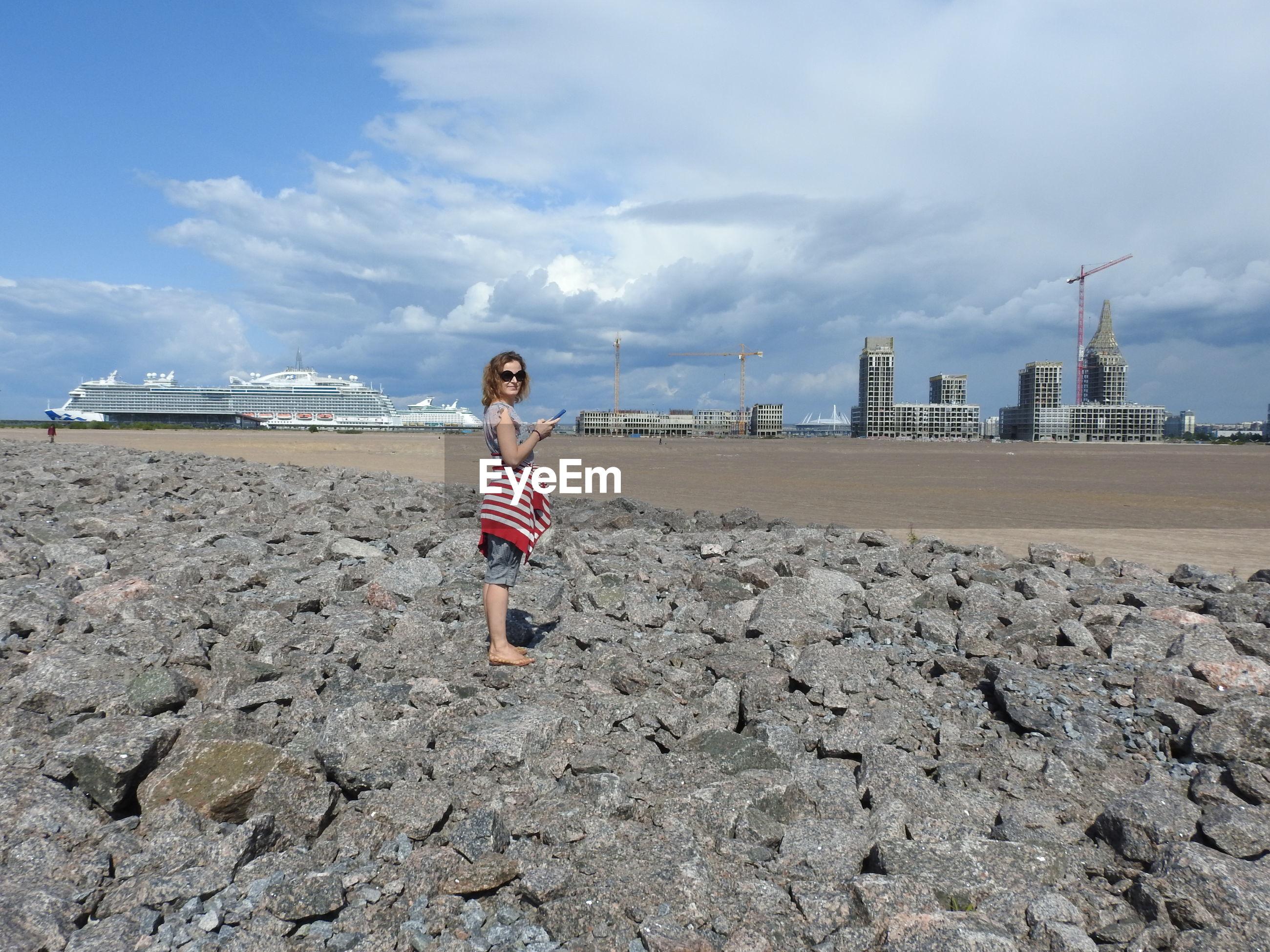 Full length of girl standing on rock at beach against sky