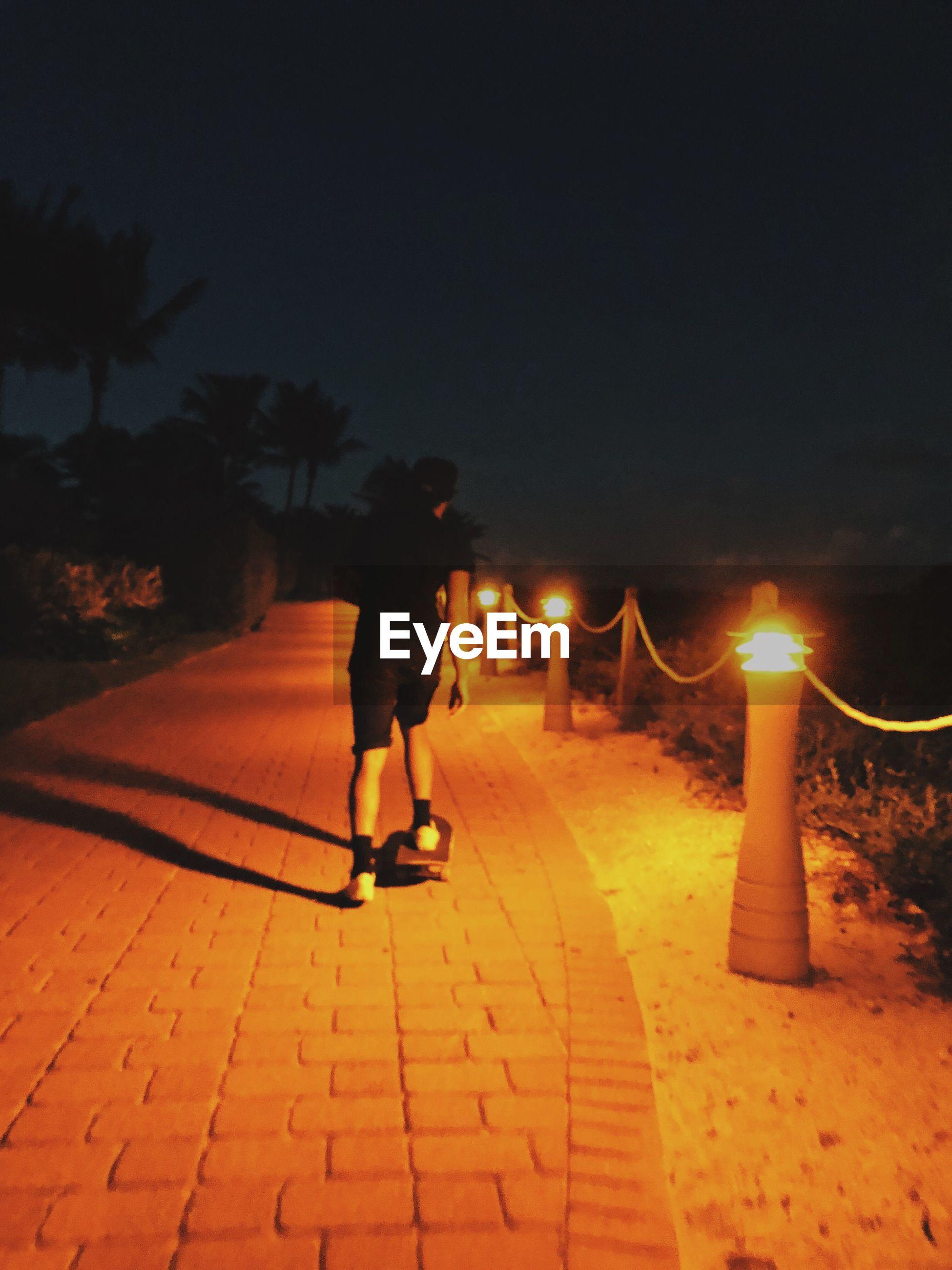 FULL LENGTH OF MAN WALKING ON ILLUMINATED ROAD AT NIGHT
