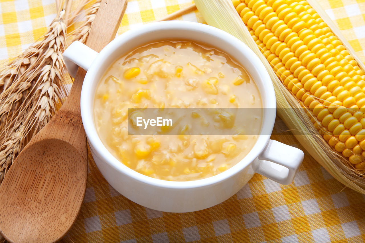 food and drink, food, still life, freshness, table, wellbeing, healthy eating, bowl, indoors, ready-to-eat, close-up, no people, corn, kitchen utensil, spoon, eating utensil, wood - material, high angle view, serving size, vegetable, sweetcorn, place mat, breakfast, temptation