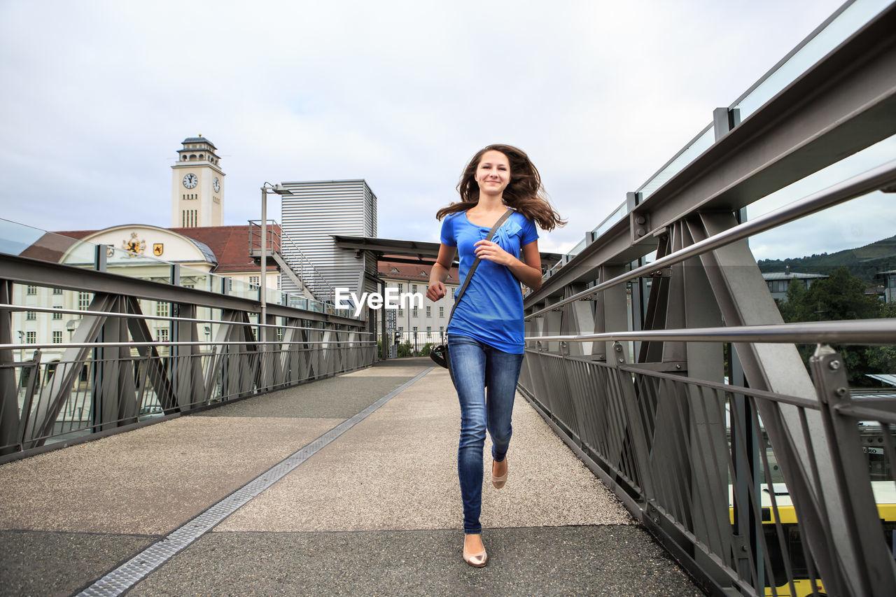 Full length of woman running on bridge against sky