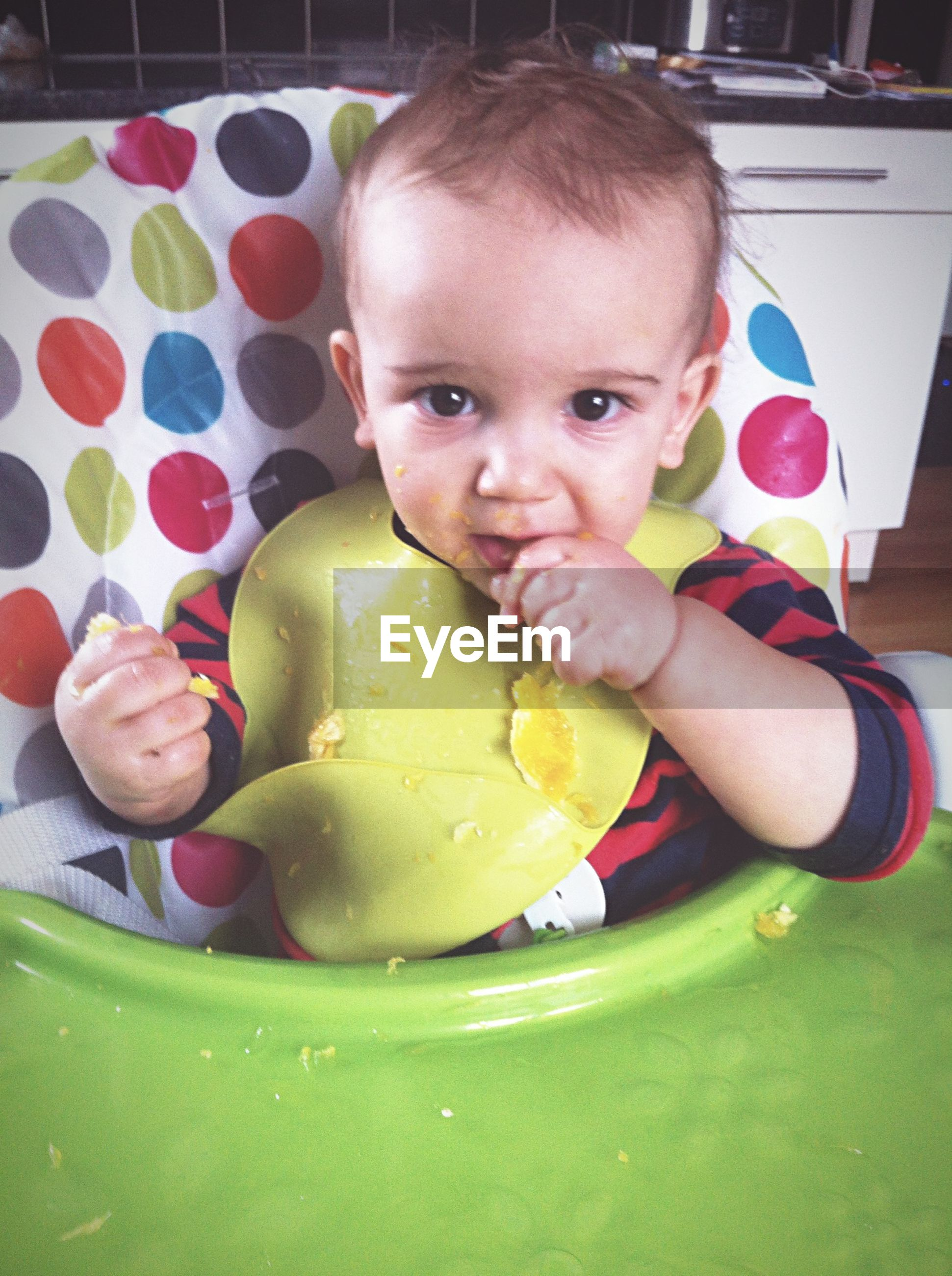 Portrait of boy eating food on high chair at home