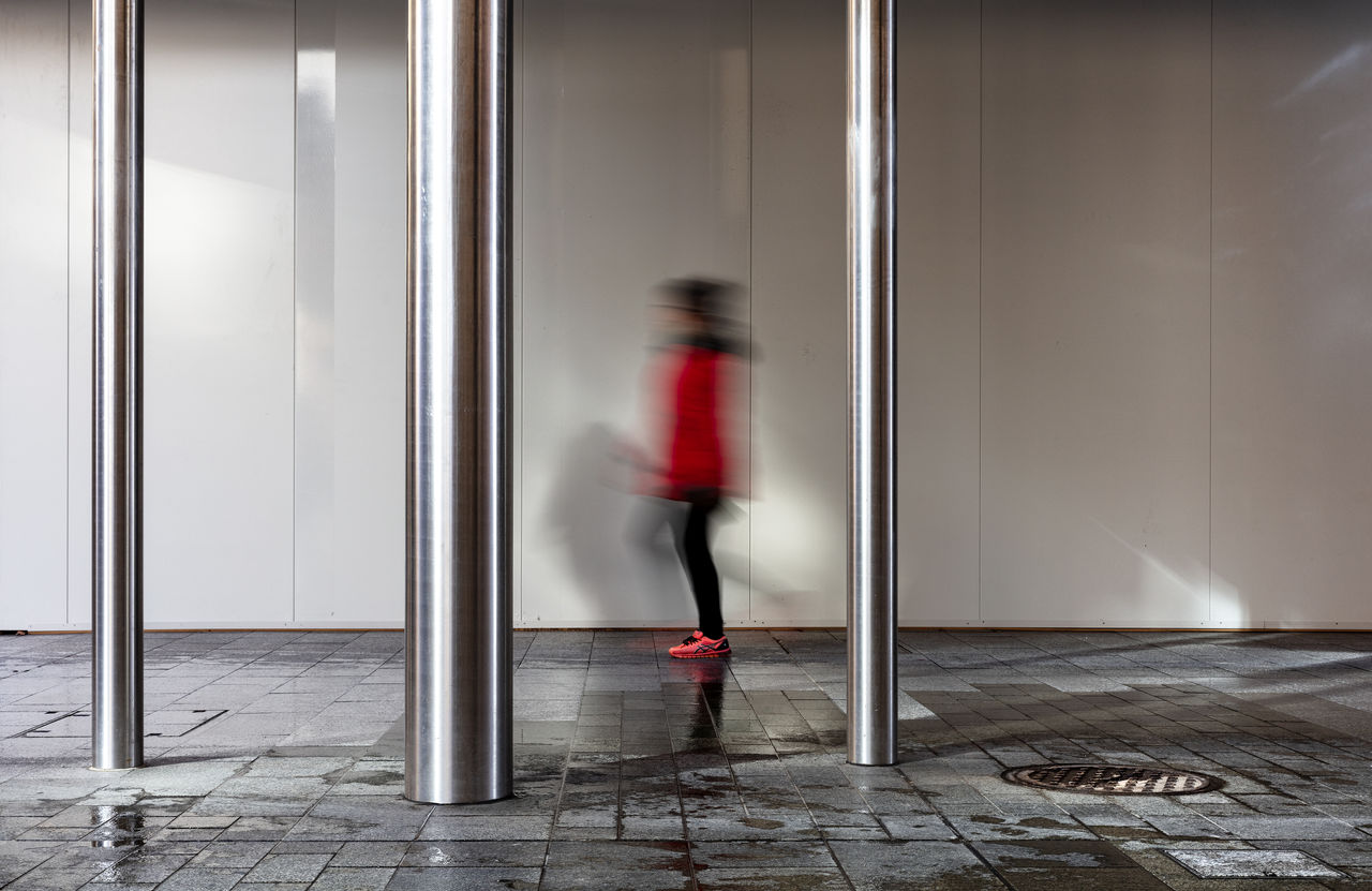 Blurred Motion Of Woman Walking In Corridor Of Building