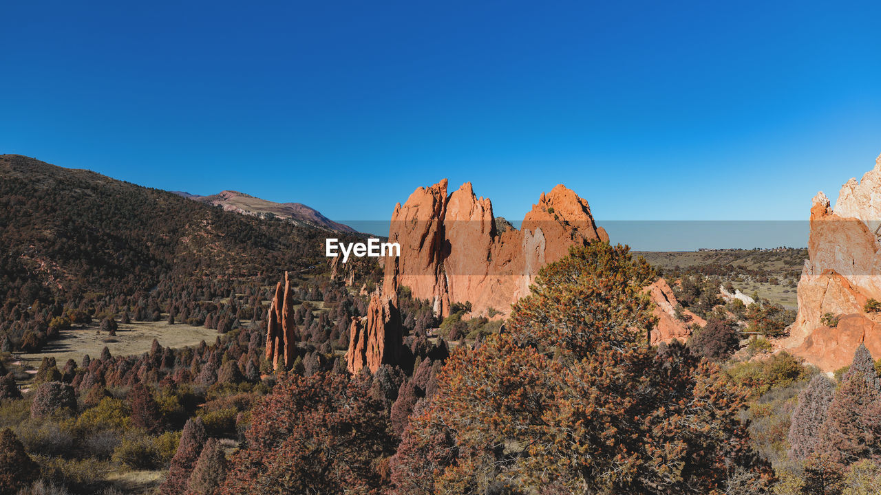 sky, beauty in nature, scenics - nature, blue, tranquil scene, tranquility, non-urban scene, mountain, clear sky, rock formation, rock, copy space, nature, plant, tree, rock - object, no people, environment, solid, remote, outdoors, climate, arid climate, formation, eroded