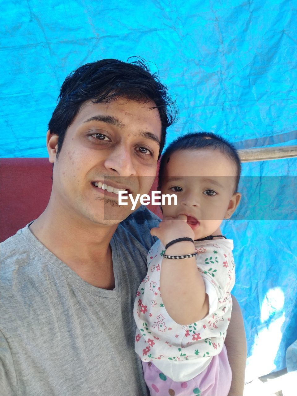 real people, looking at camera, baby, portrait, family with one child, togetherness, bonding, leisure activity, father, lifestyles, son, swimming pool, happiness, love, young adult, cute, childhood, day, indoors, smiling, young women, water, close-up