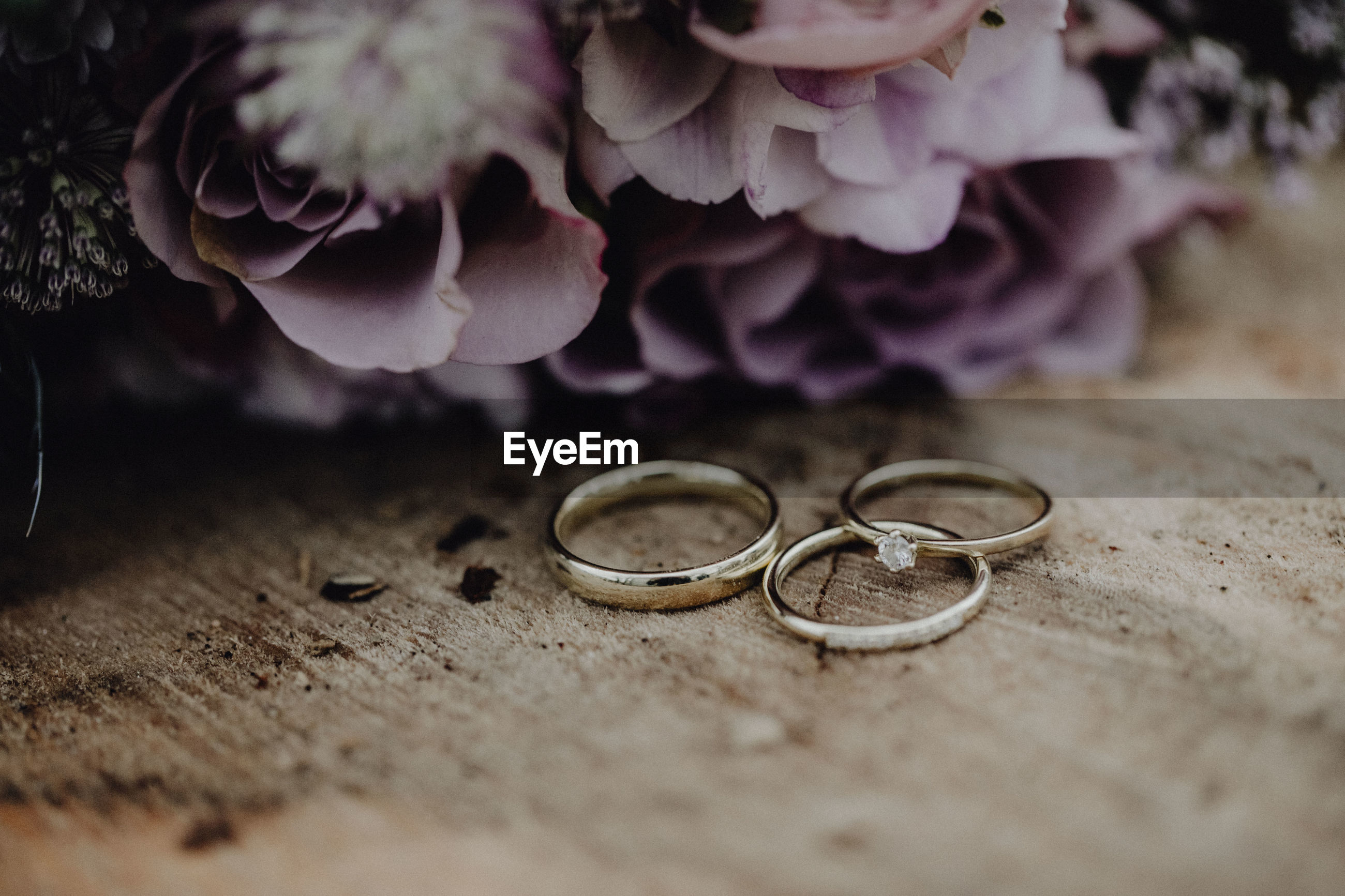 Close-up of wedding rings by flowers on wooden table