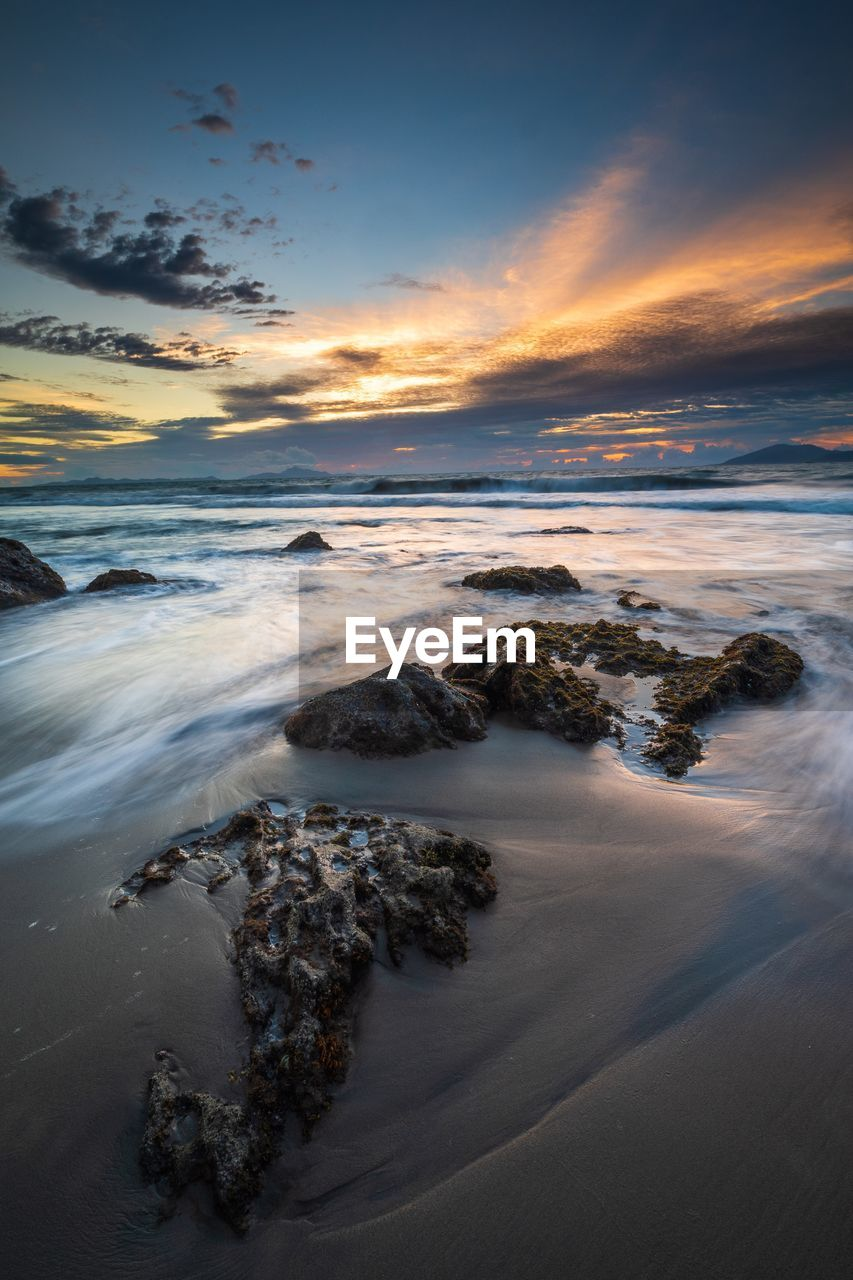 sky, sea, water, beauty in nature, beach, land, sunset, cloud - sky, scenics - nature, tranquility, tranquil scene, nature, motion, horizon over water, no people, rock, rock - object, solid, sand, outdoors