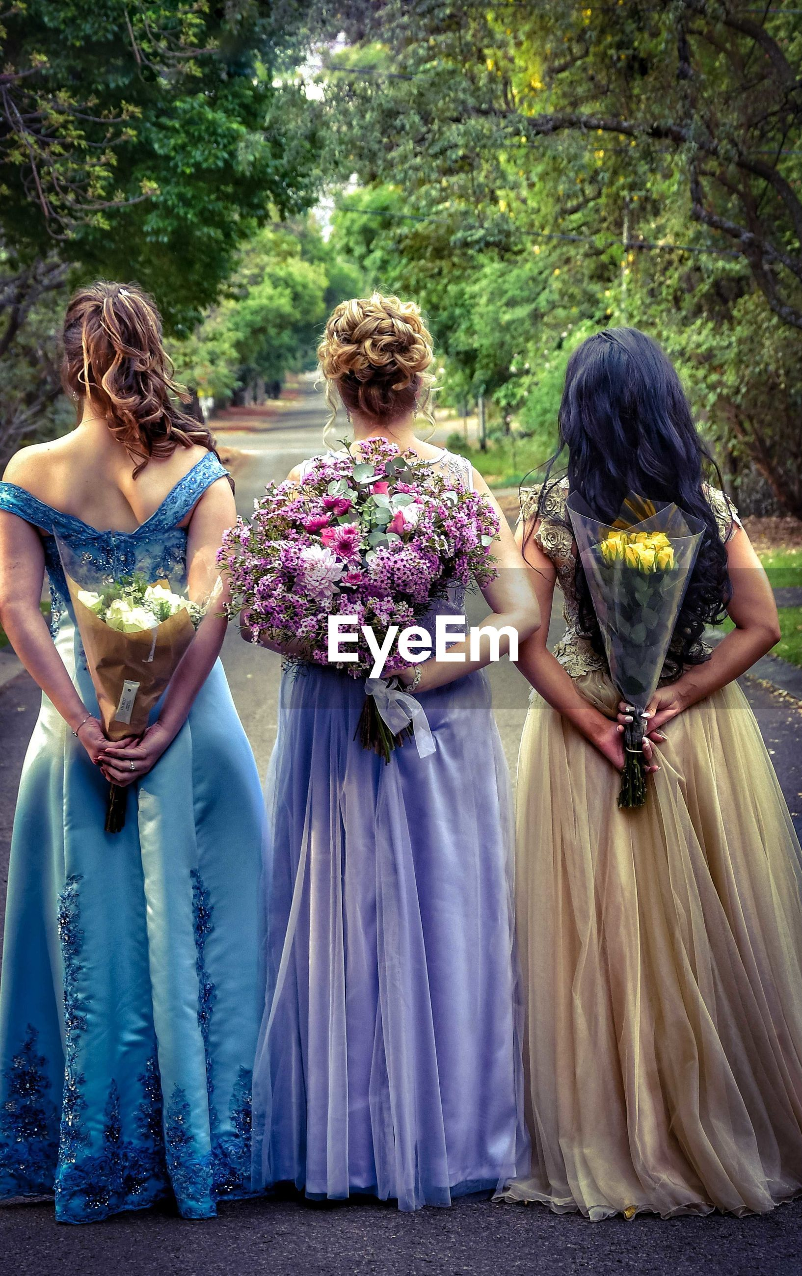 REAR VIEW OF WOMEN STANDING WITH FLOWERS IN FOREGROUND