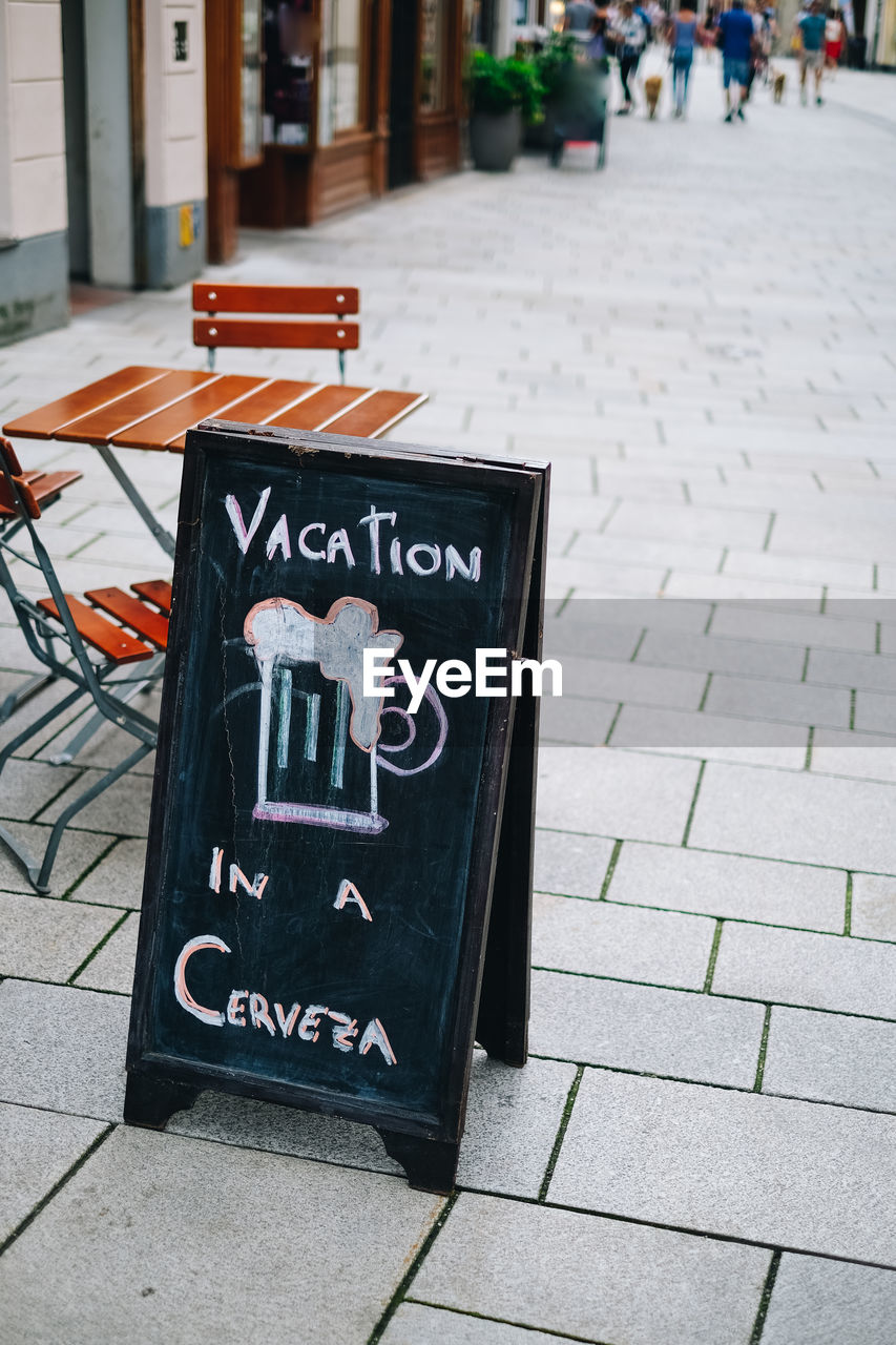 text, communication, western script, sign, incidental people, footpath, day, street, sidewalk, information, information sign, city, board, non-western script, script, outdoors, focus on foreground, architecture, blackboard, message, paving stone, menu