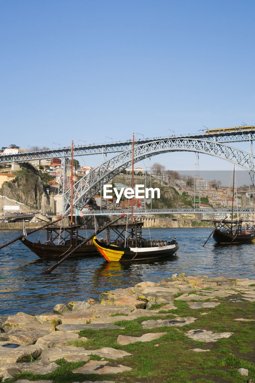 water, sky, nautical vessel, transportation, clear sky, architecture, copy space, nature, mode of transportation, built structure, day, river, moored, no people, travel, sunlight, building exterior, bridge, connection, outdoors, port, sailboat, location