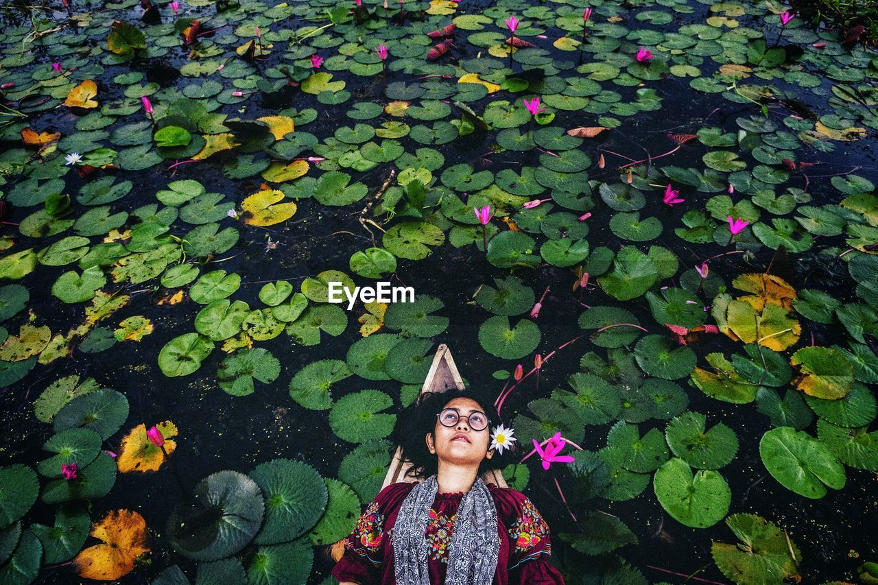 High angle view of woman lying on boat in lake