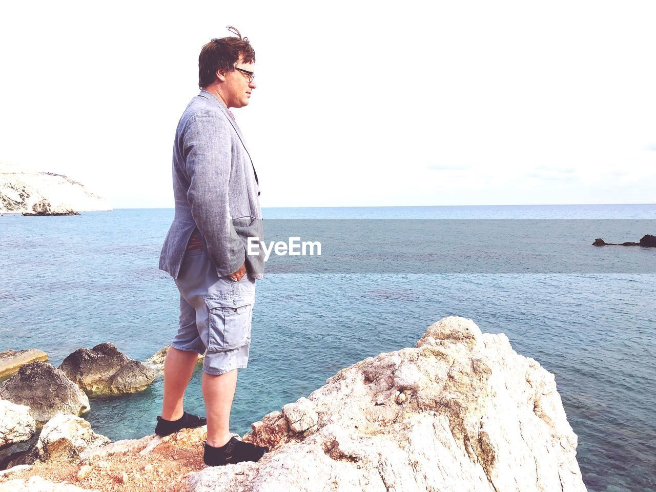 Side View Of Mature Man Looking At Sea While Standing On Rock Against Clear Sky