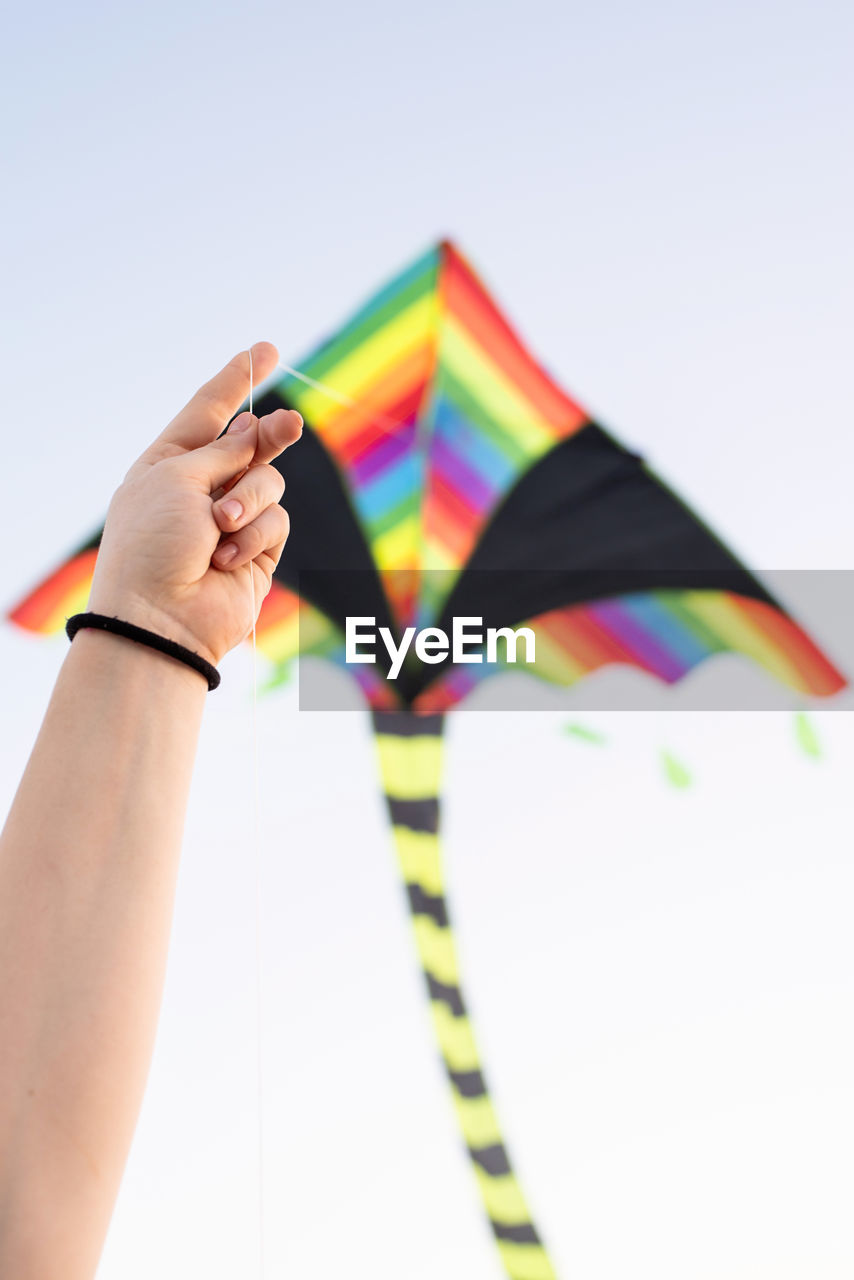 Midsection of person holding multi colored flag against clear sky
