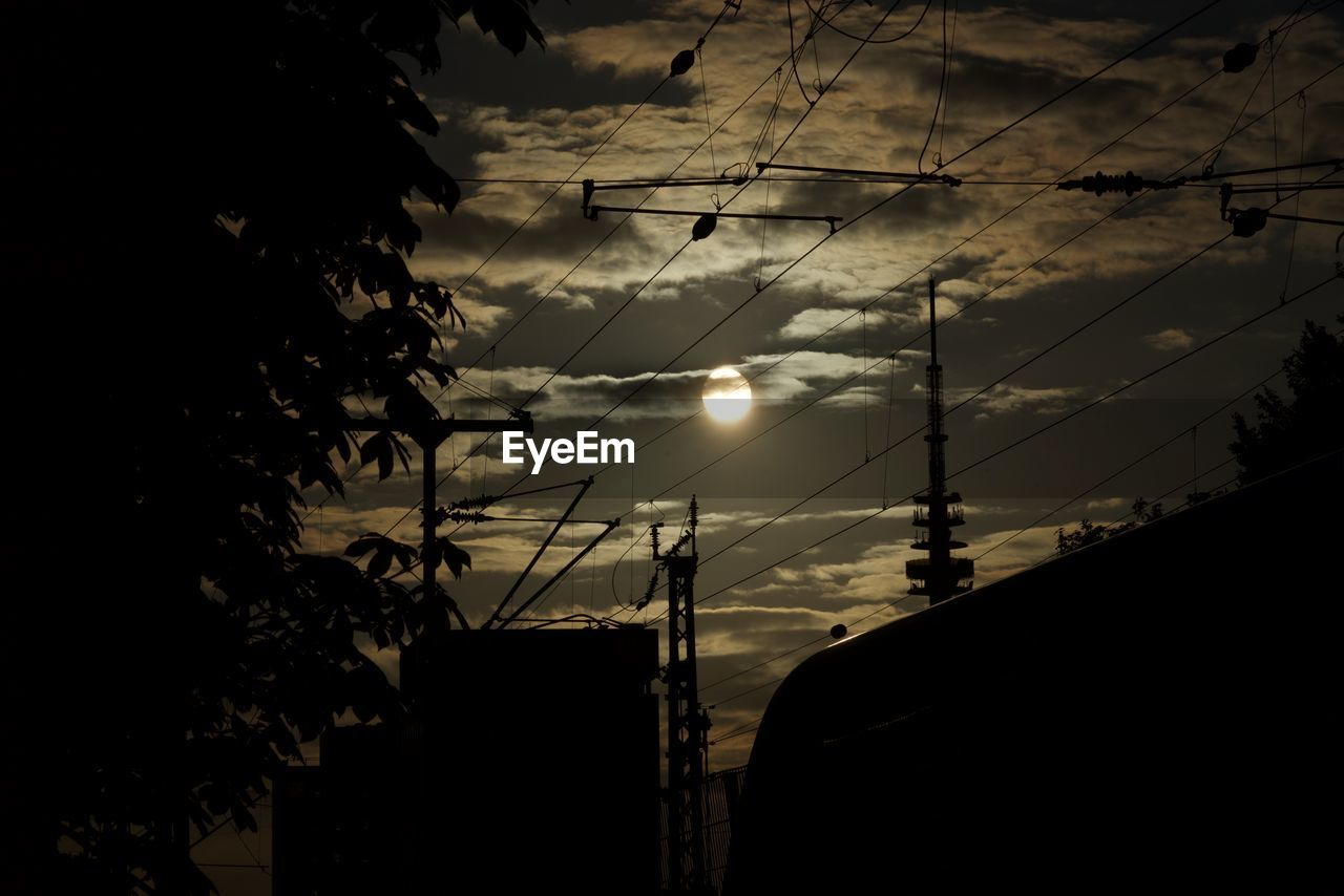 connection, cable, silhouette, sky, power line, electricity, power supply, building exterior, built structure, architecture, cloud - sky, technology, low angle view, no people, sunset, fuel and power generation, electricity pylon, outdoors, nature, antenna - aerial, growth, television aerial, tree, beauty in nature, telephone line, day