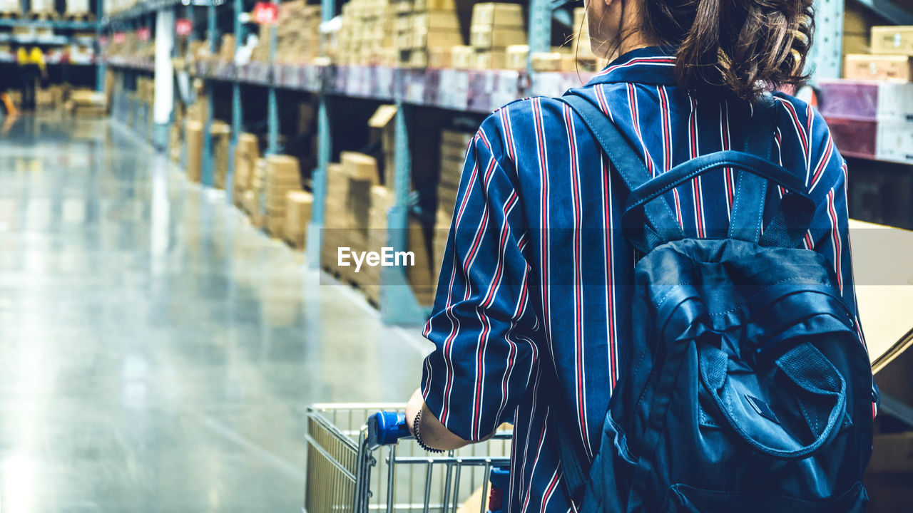 Midsection Of Woman With Shopping Cart Walking In Supermarket
