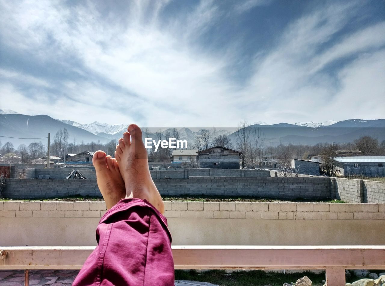 Low section of man with feet up of railing against sky