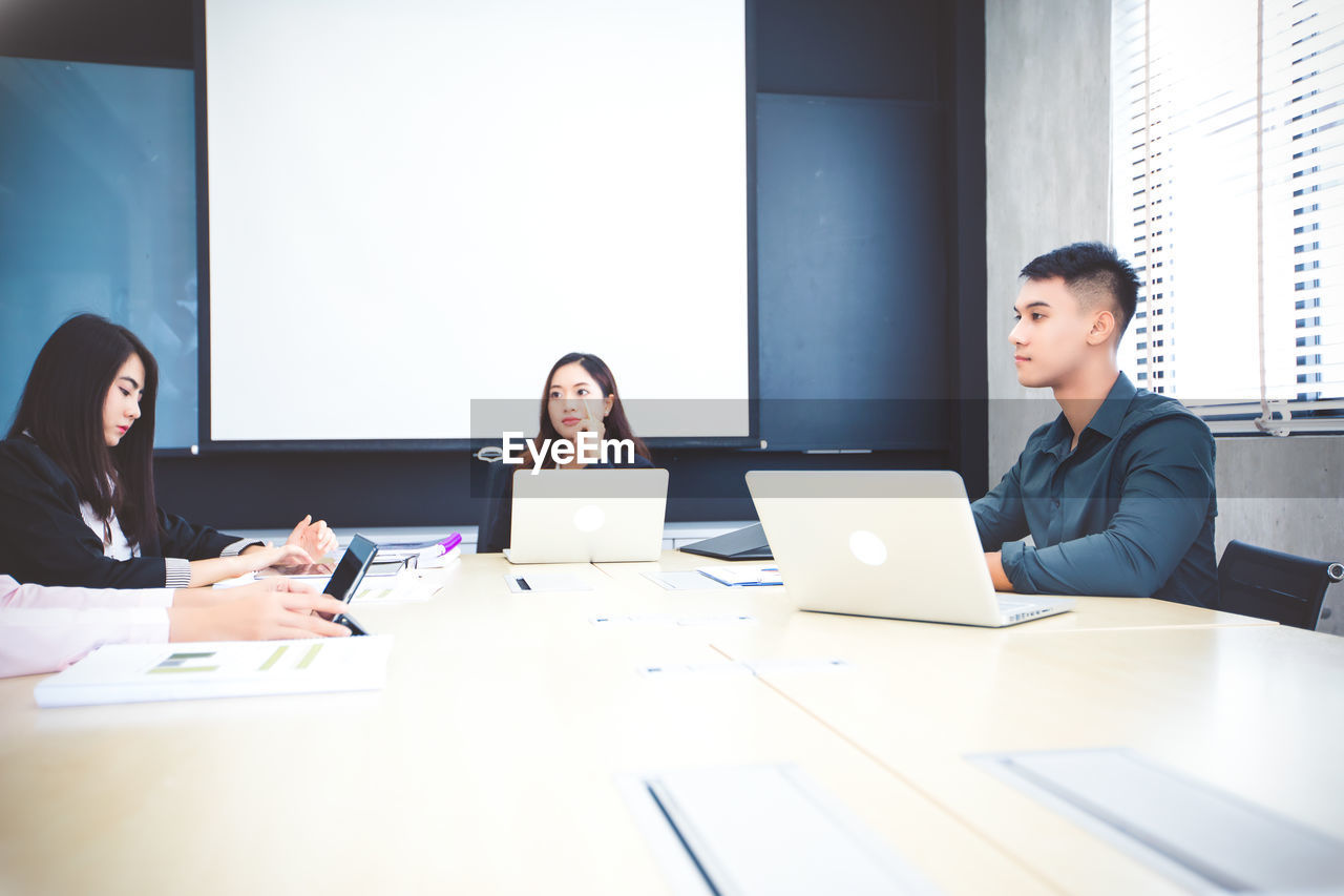 Colleagues discussing at table in conference room