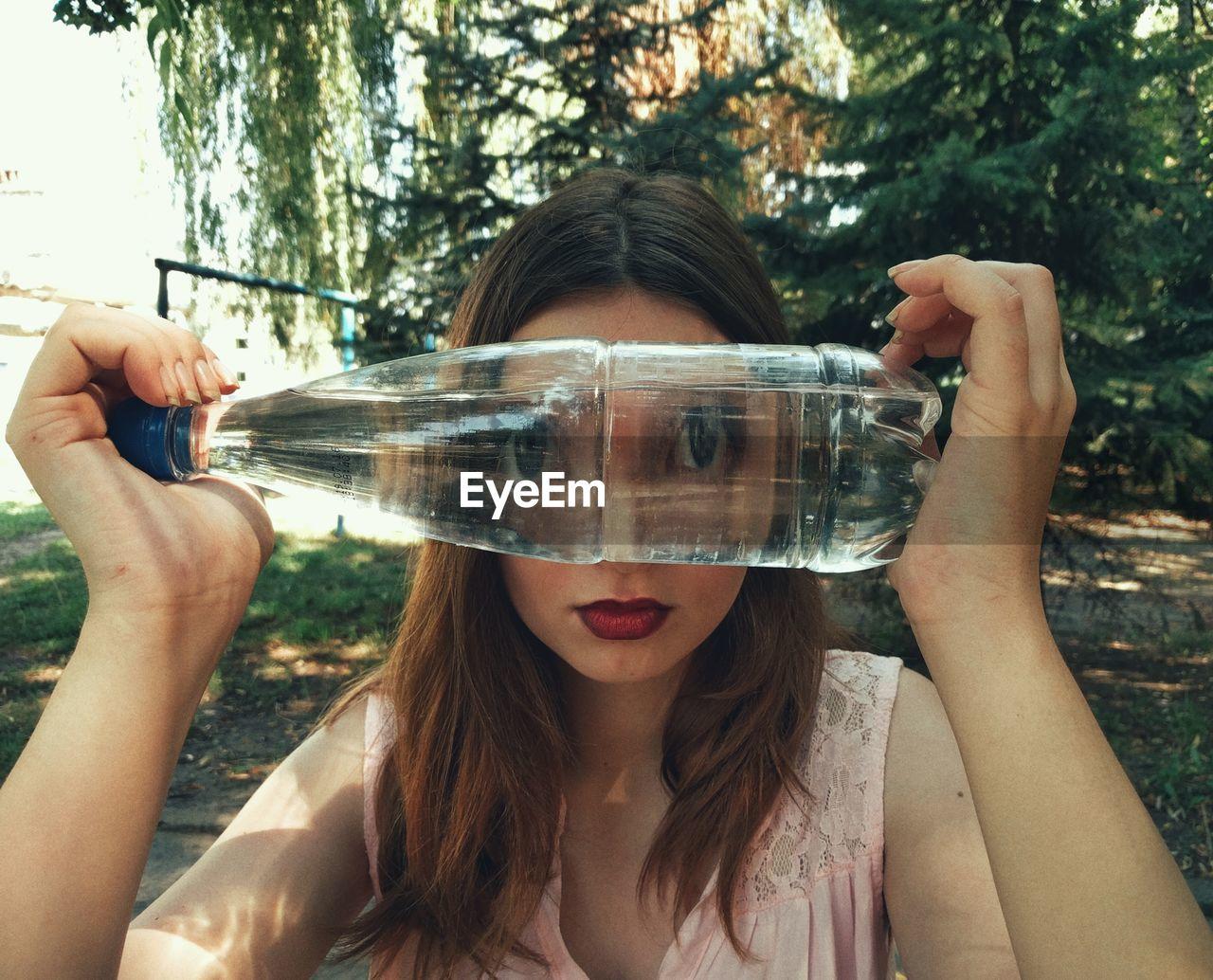 Portrait Of Woman Looking Through Water Bottle