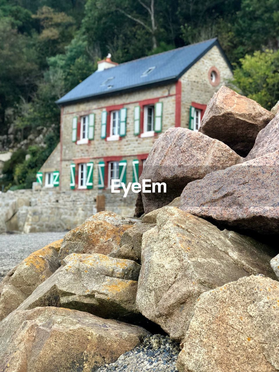 solid, built structure, rock, architecture, rock - object, no people, house, building exterior, nature, day, building, stone - object, outdoors, focus on foreground, tree, water, stone material, residential district, land, plant