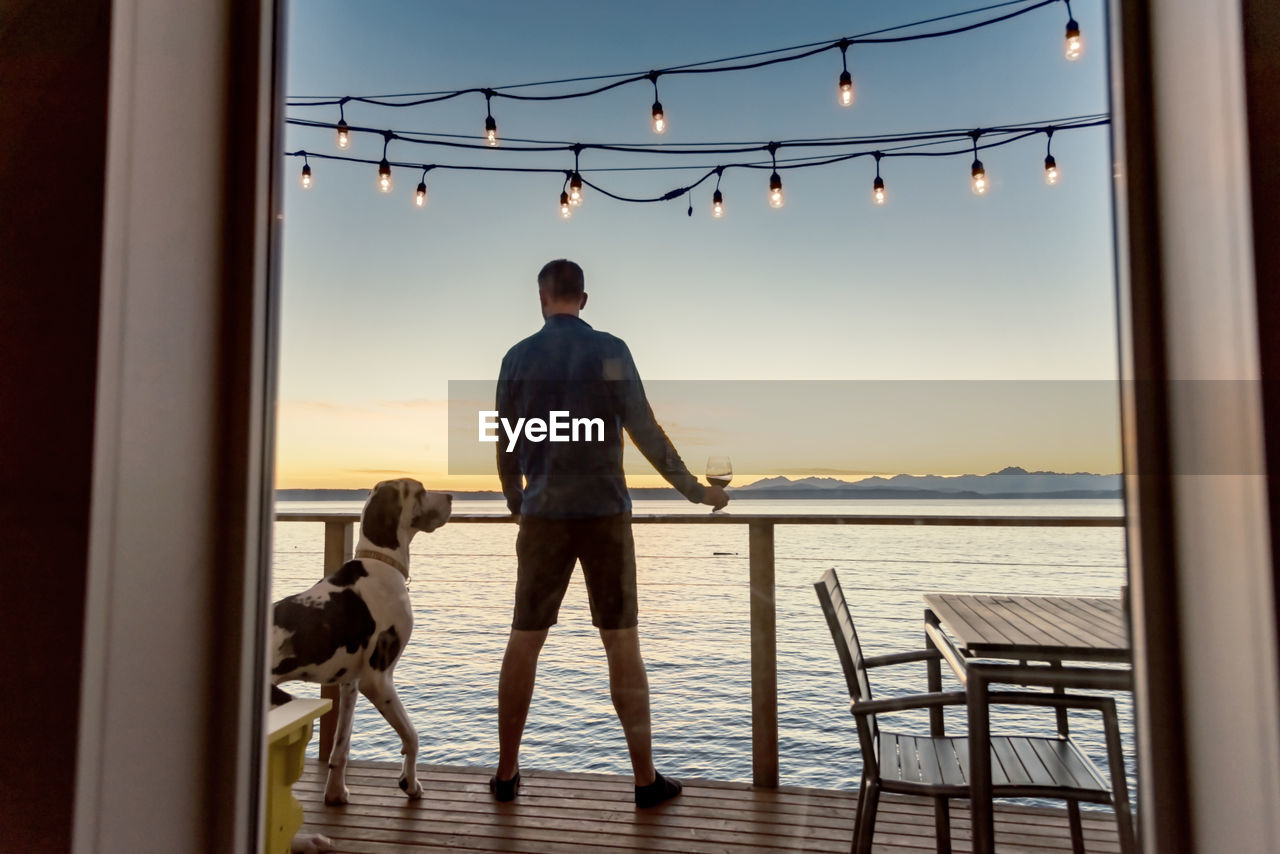 Man with dog standing in boat deck over sea against sky