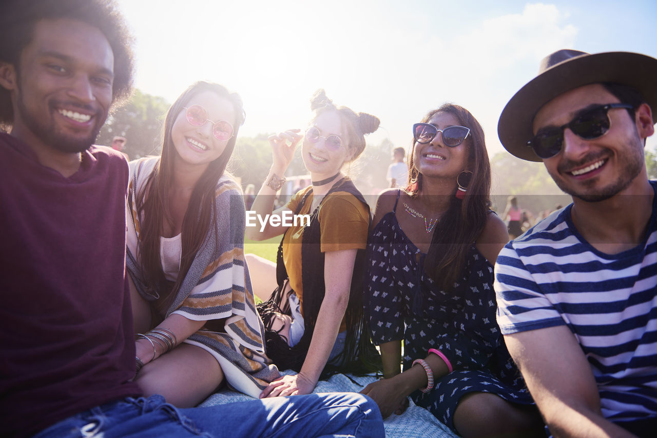 smiling, happiness, young adult, friendship, group of people, leisure activity, lifestyles, enjoyment, emotion, young men, young women, casual clothing, sitting, real people, fun, togetherness, teeth, toothy smile, women, fashion, outdoors, music festival, festival