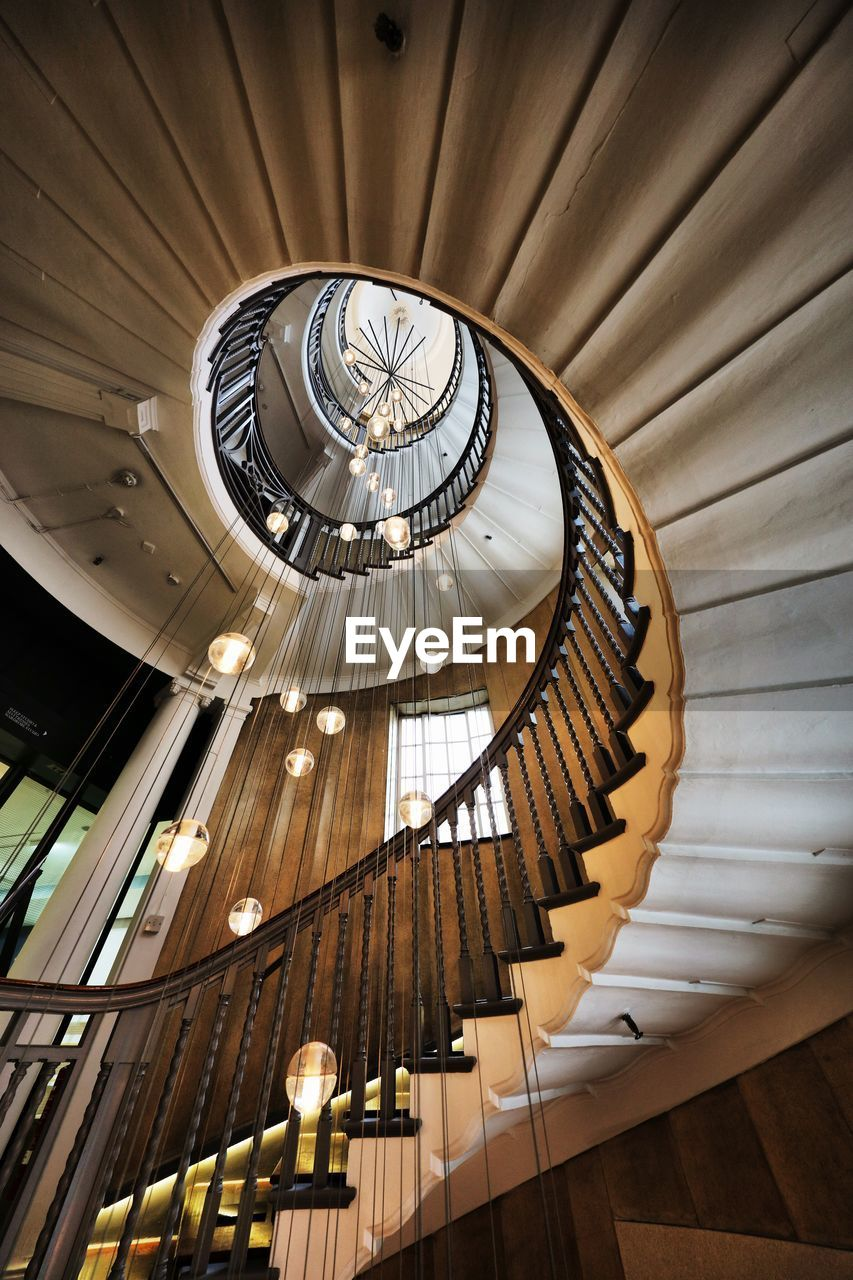 architecture, built structure, staircase, indoors, steps and staircases, low angle view, ceiling, railing, spiral, pattern, no people, design, architectural feature, spiral staircase, lighting equipment, wood - material, decoration, directly below, building, hanging, skylight, ornate, cupola, architecture and art, luxury