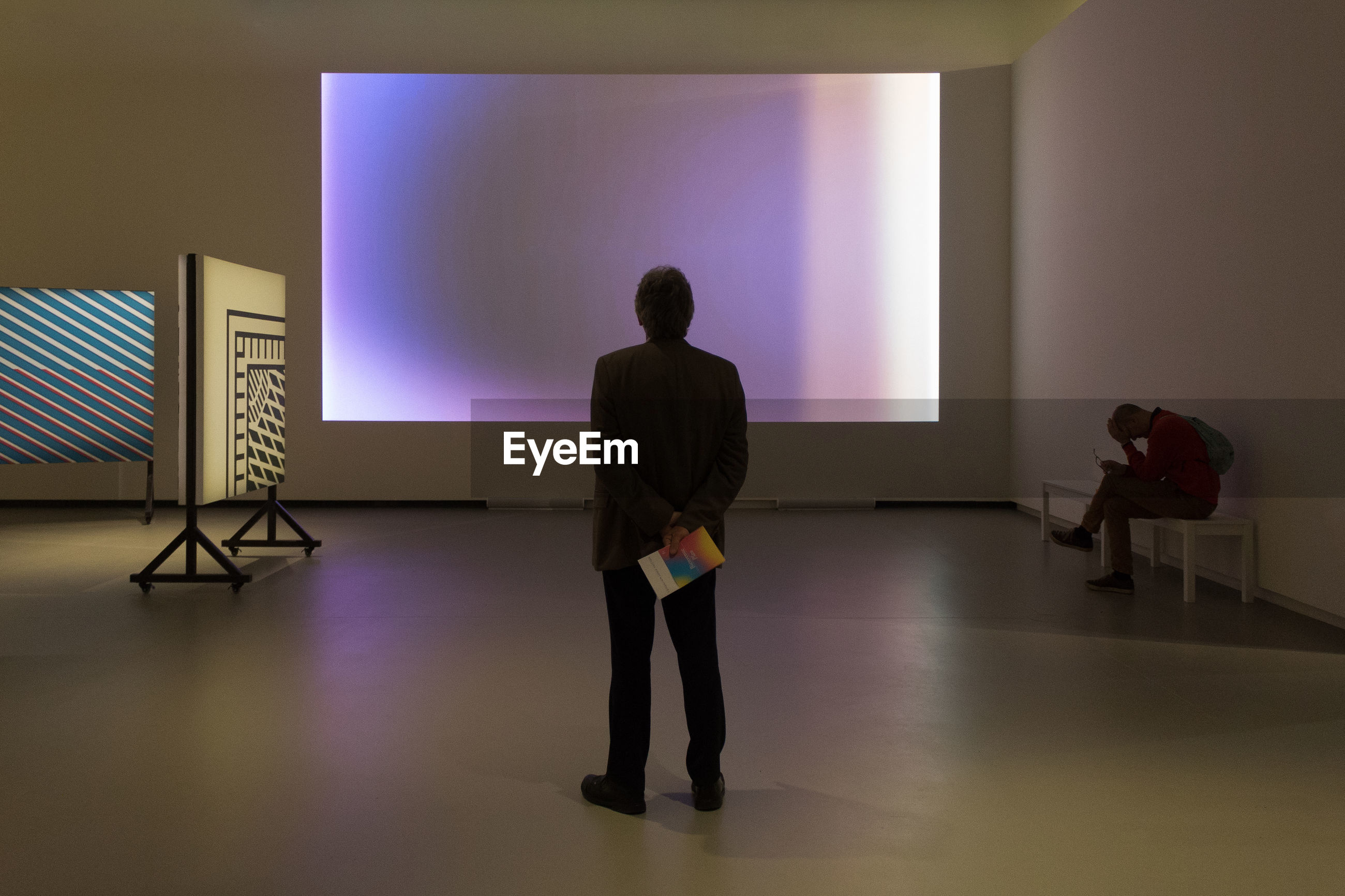 REAR VIEW OF WOMAN WORKING AT ILLUMINATED ROOM