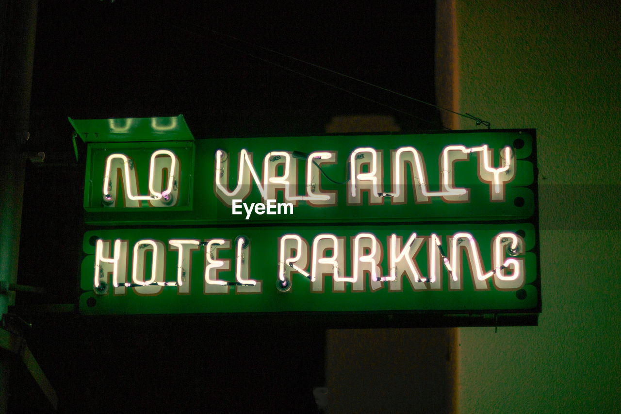 text, western script, communication, illuminated, capital letter, green color, no people, night, neon, sign, information, low angle view, information sign, lighting equipment, close-up, outdoors, architecture, guidance, light - natural phenomenon, nightlife