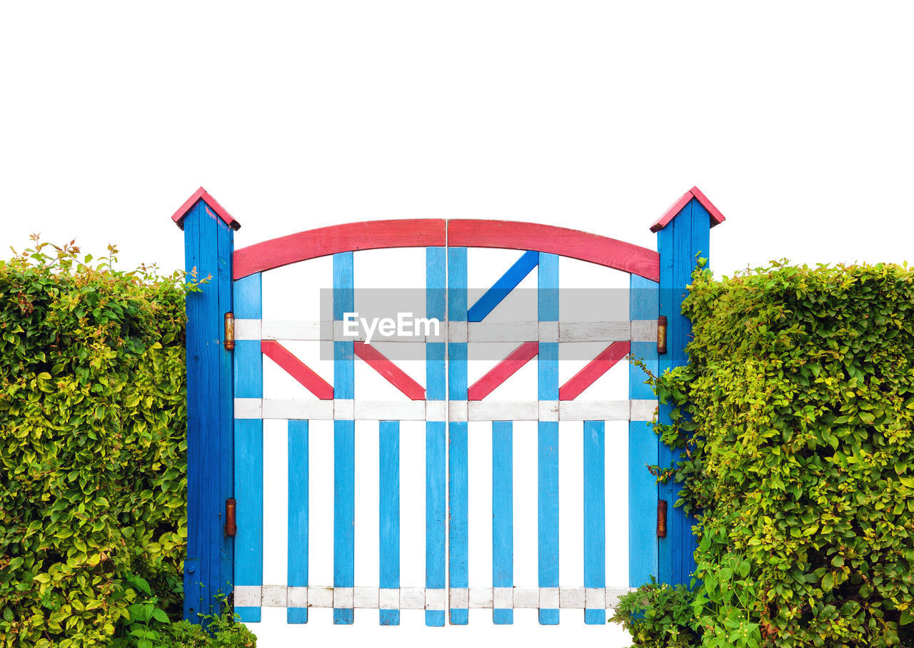 red, built structure, multi colored, day, architecture, building exterior, nature, communication, no people, sky, text, blue, striped, sign, outdoors, plant, western script, clear sky, capital letter, tree