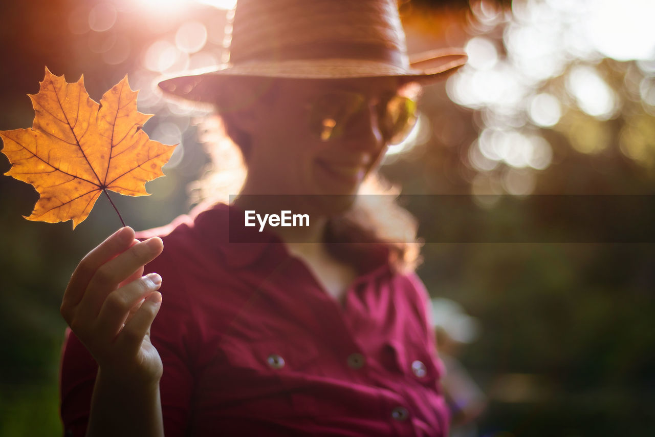 Young Woman Showing Maple Leaf During Autumn