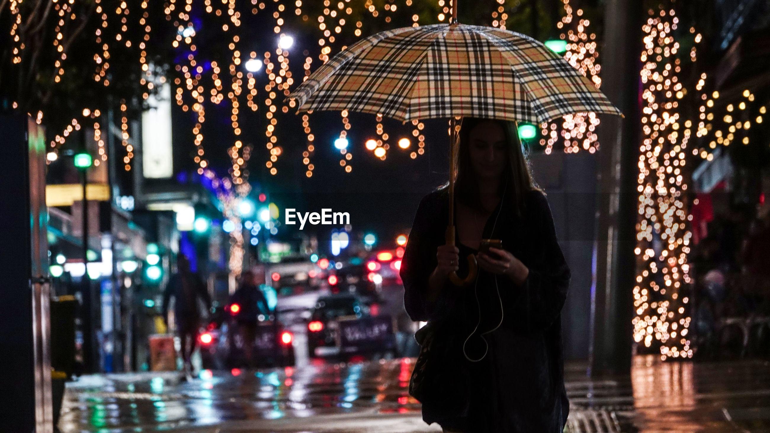 WOMAN STANDING ON ILLUMINATED STREET DURING RAINY SEASON