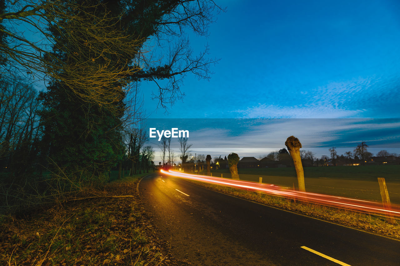 transportation, tree, road, plant, direction, sky, the way forward, nature, no people, blue, diminishing perspective, illuminated, street, tranquility, mode of transportation, outdoors, beauty in nature, city, dusk, tranquil scene