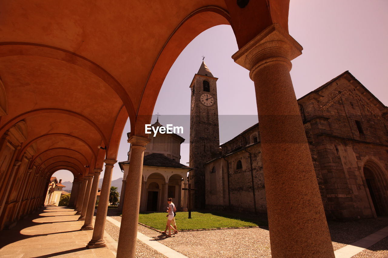 Empty Colonnade In Church By Bell Tower Against Sky