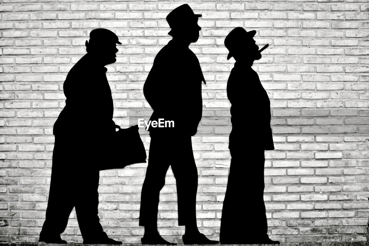 silhouette, brick wall, real people, men, standing, togetherness, lifestyles, full length, shadow, day, outdoors, friendship, women, bonding, building exterior, architecture, adult, people