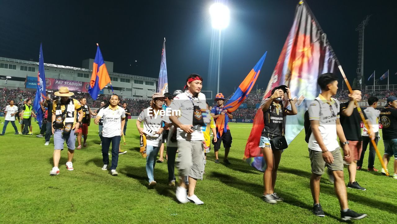 large group of people, real people, celebration, full length, flag, leisure activity, togetherness, night, outdoors, lifestyles, grass, young women, young adult, people, adult