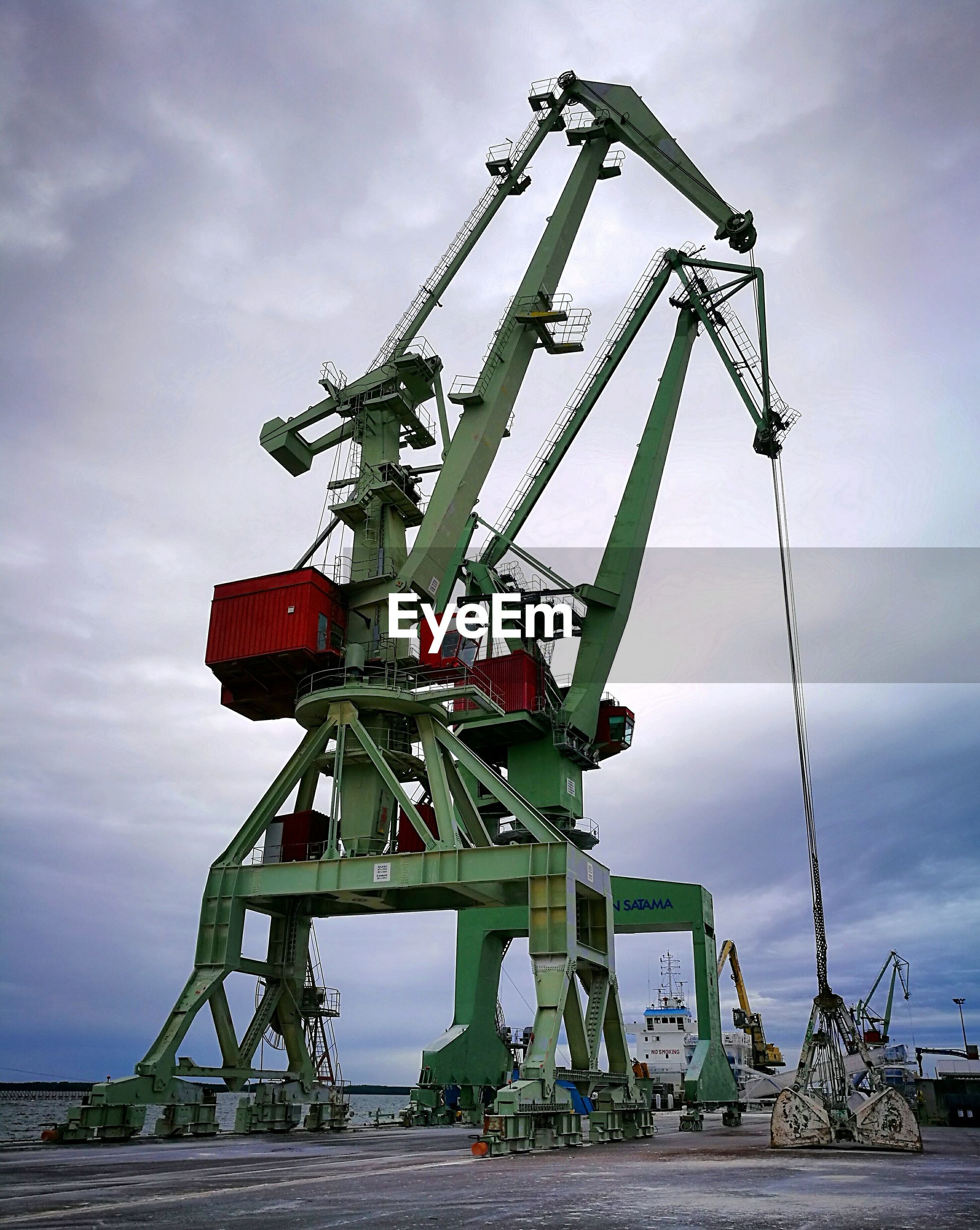Low angle view of cranes at harbor against sky