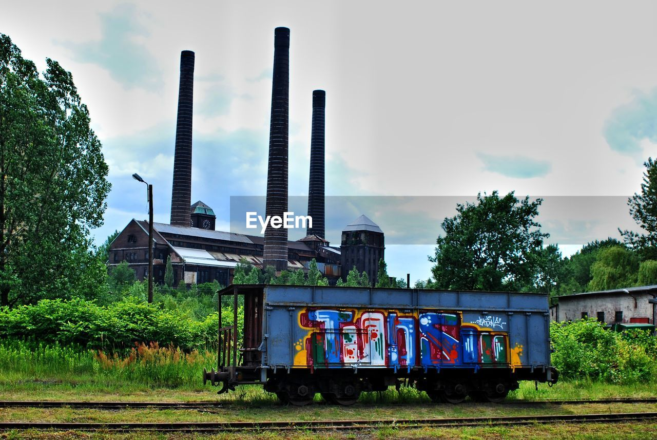 tree, rail transportation, sky, built structure, day, train - vehicle, transportation, industry, no people, outdoors, architecture, railroad track, factory, growth, building exterior