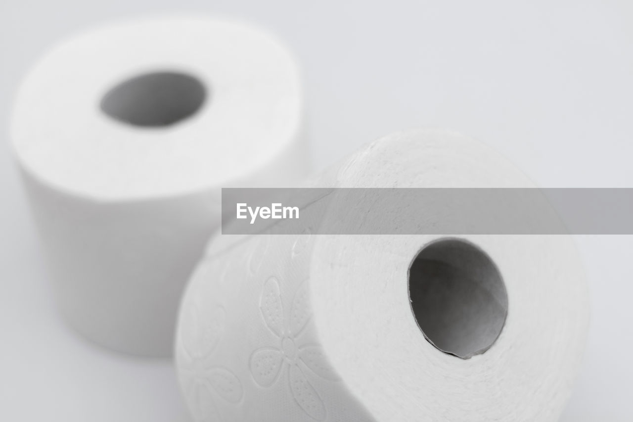 toilet paper, indoors, close-up, still life, rolled up, no people, hygiene, studio shot, high angle view, white background, white color, bathroom, circle, hole, shape, paper, geometric shape, focus on foreground, single object, design, electrical equipment