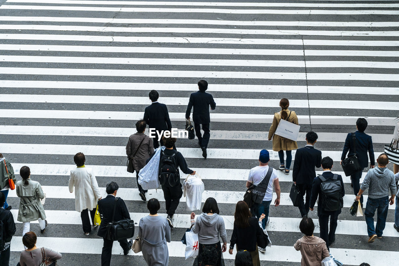 group of people, crowd, large group of people, real people, city, crosswalk, zebra crossing, crossing, road marking, road, transportation, walking, architecture, day, street, high angle view, men, symbol, city life, women, outdoors, busy