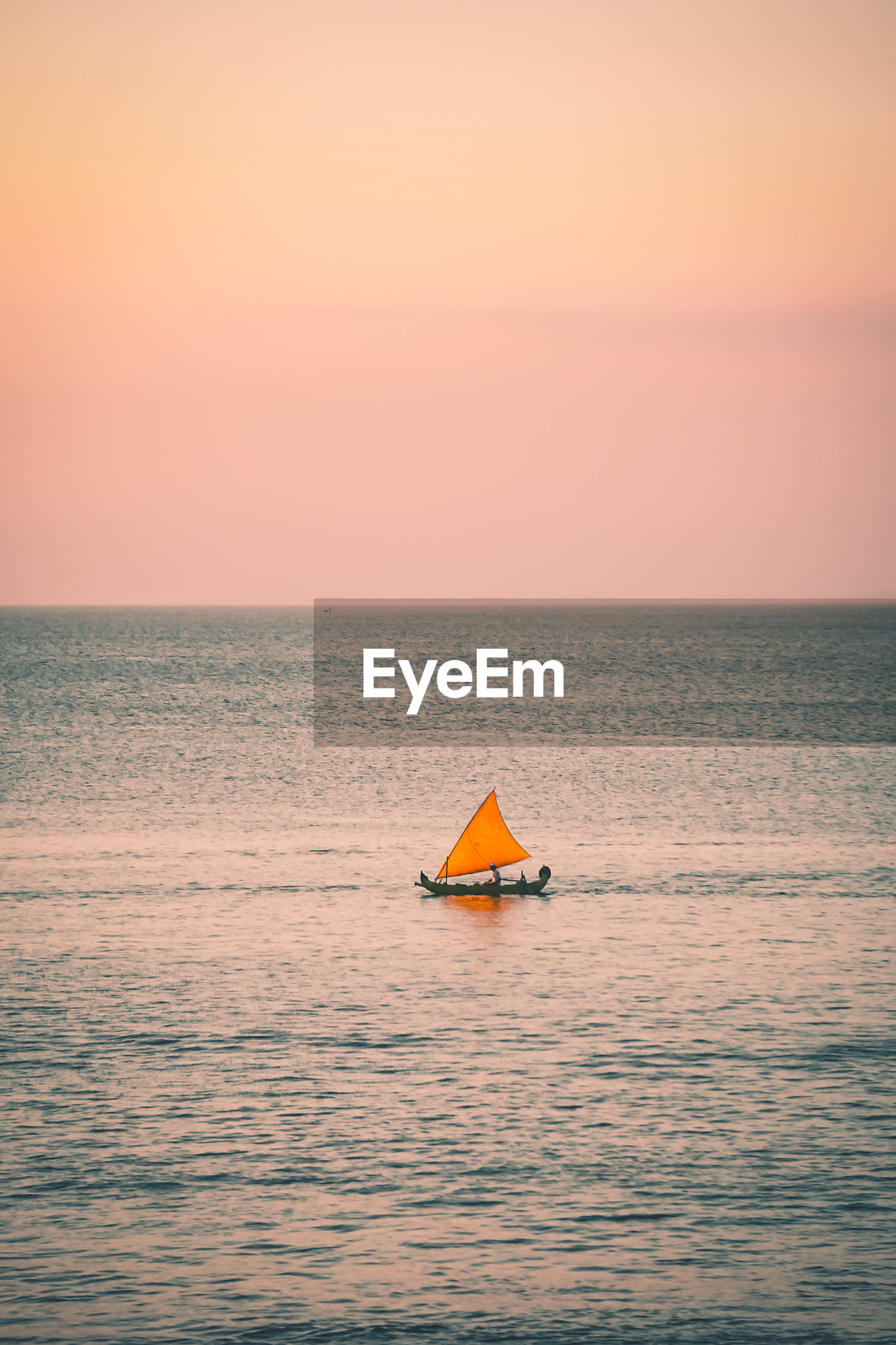 Distant view of man sailing boat in sea against orange sky