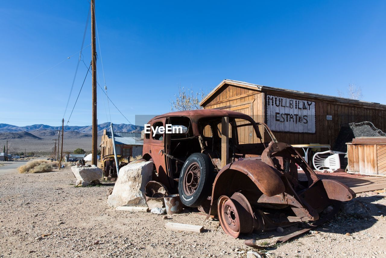 transportation, abandoned, mode of transportation, sky, day, land vehicle, clear sky, obsolete, nature, sunlight, run-down, decline, damaged, deterioration, blue, old, rusty, land, no people, motor vehicle, outdoors, junkyard