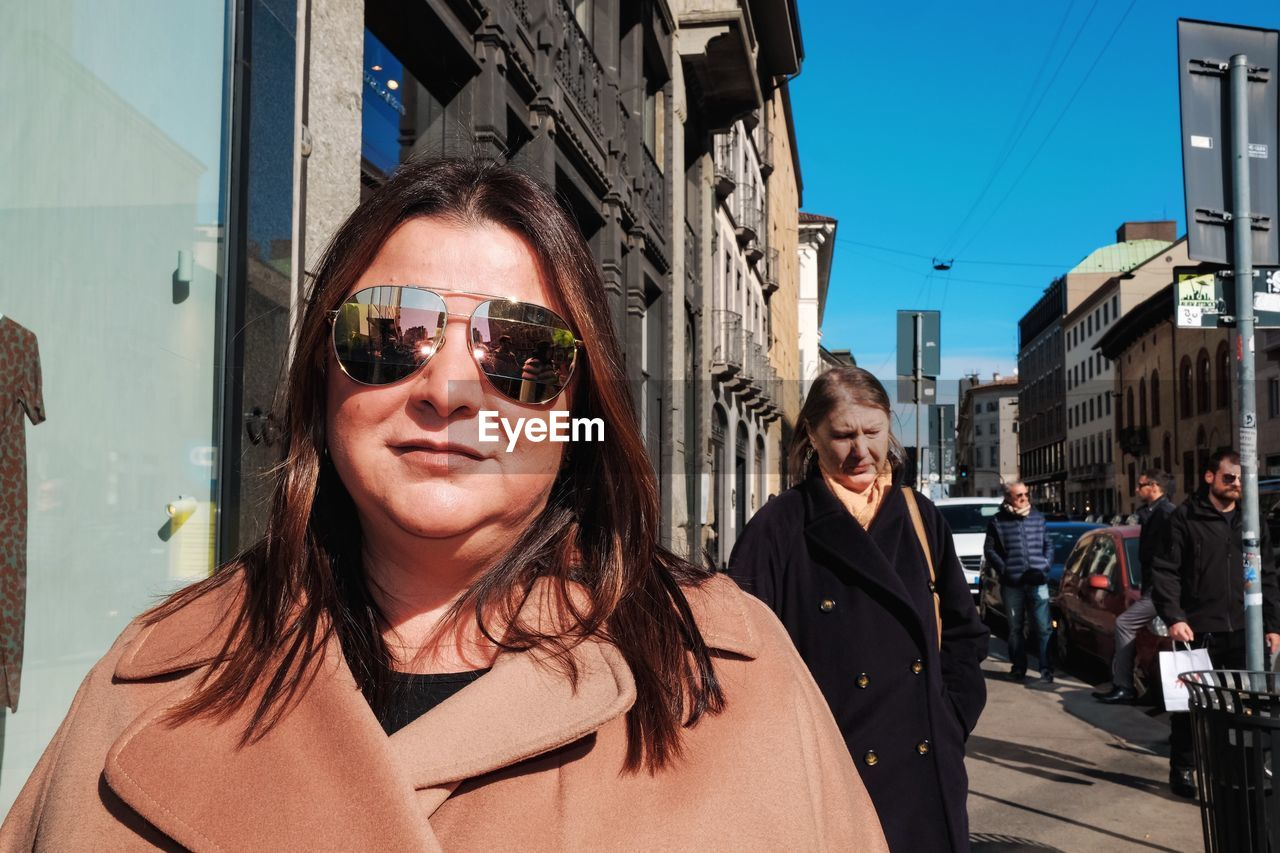 portrait, real people, looking at camera, lifestyles, architecture, sunglasses, leisure activity, glasses, headshot, young adult, city, people, building exterior, built structure, adult, incidental people, women, young women, fashion, outdoors, hairstyle