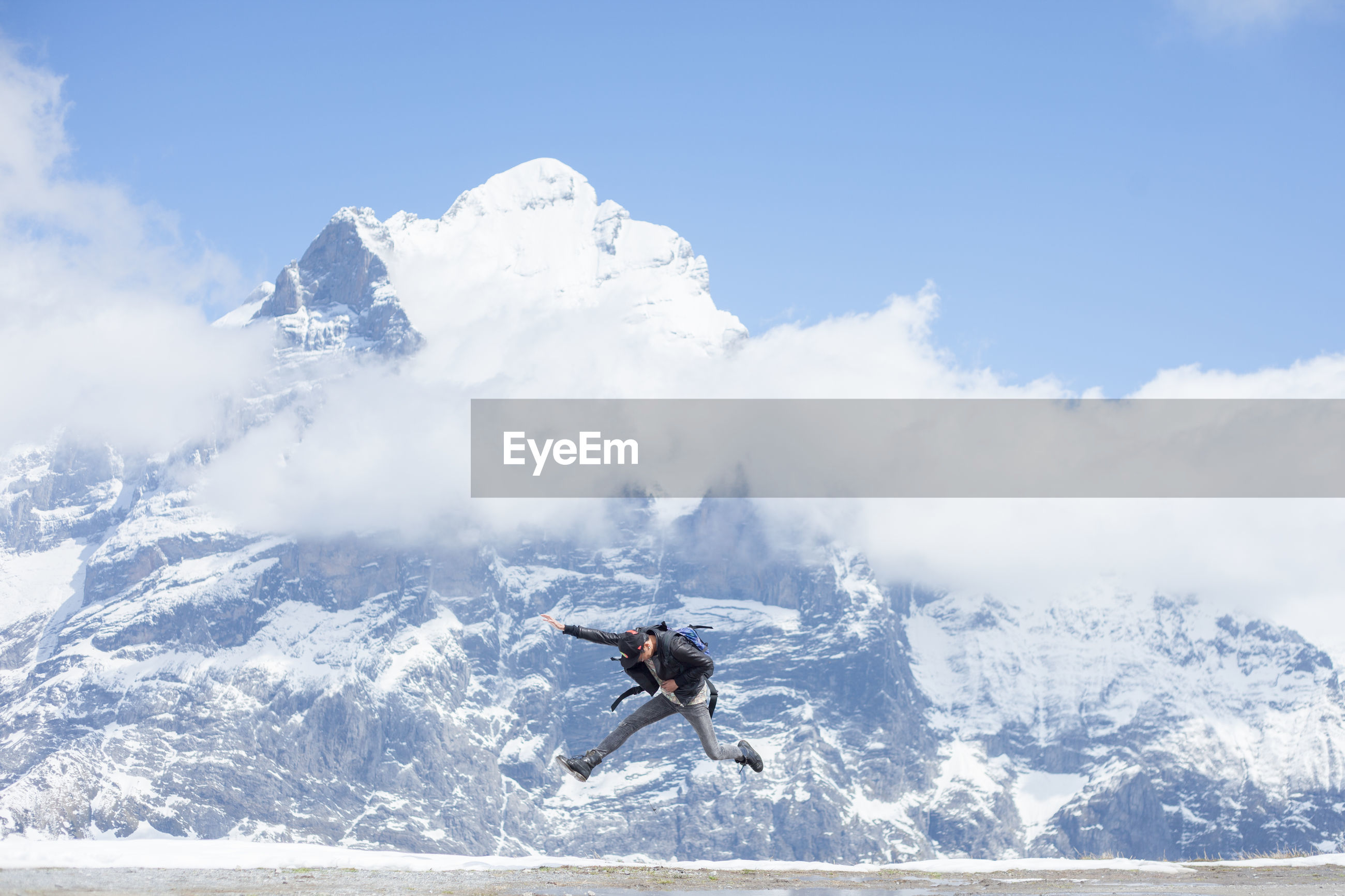 Excited man jumping against snow covered mountain